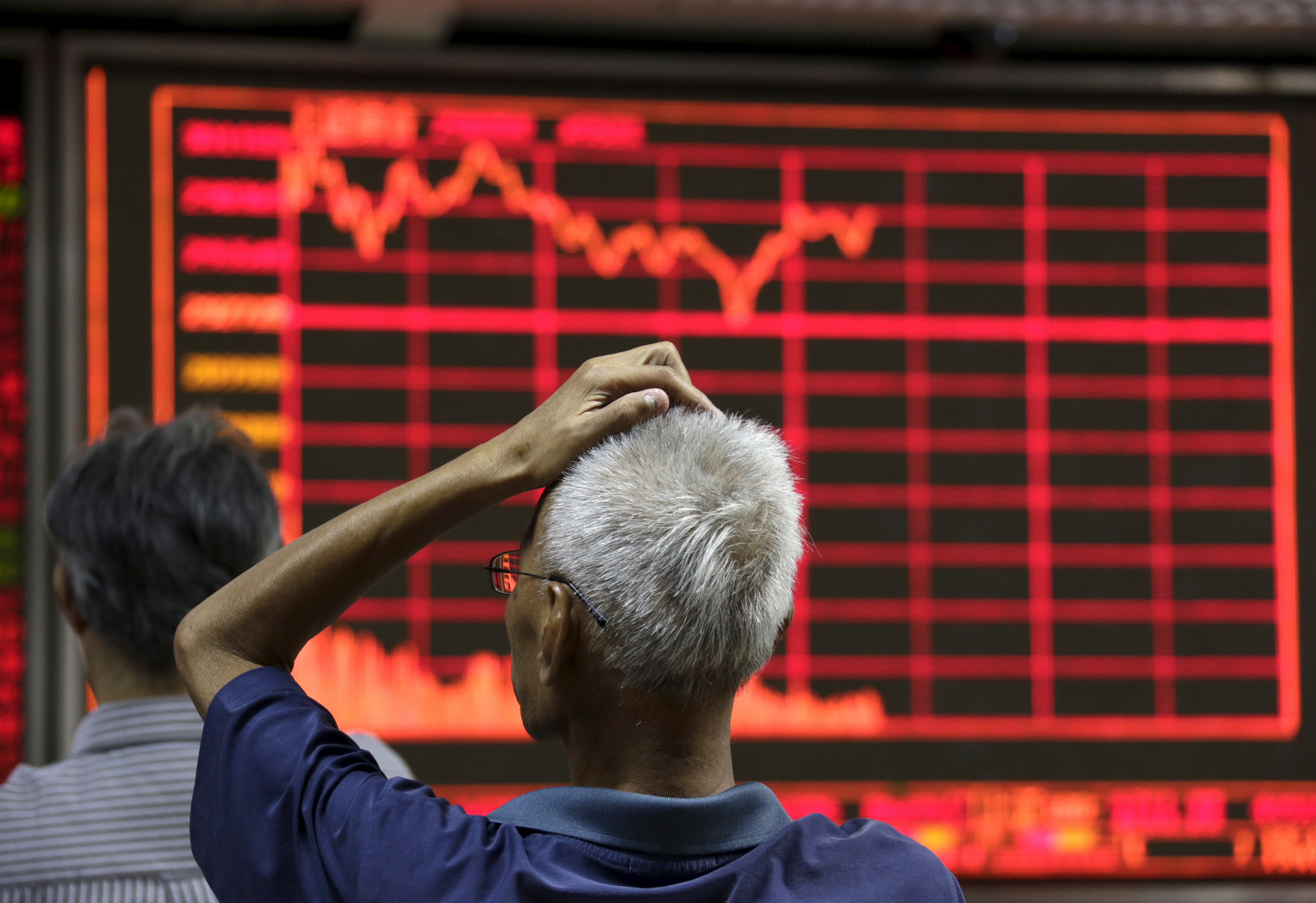 An investor looks at an electronic board showing stock information at a brokerage house in Beijing on Aug. 27, 2015.