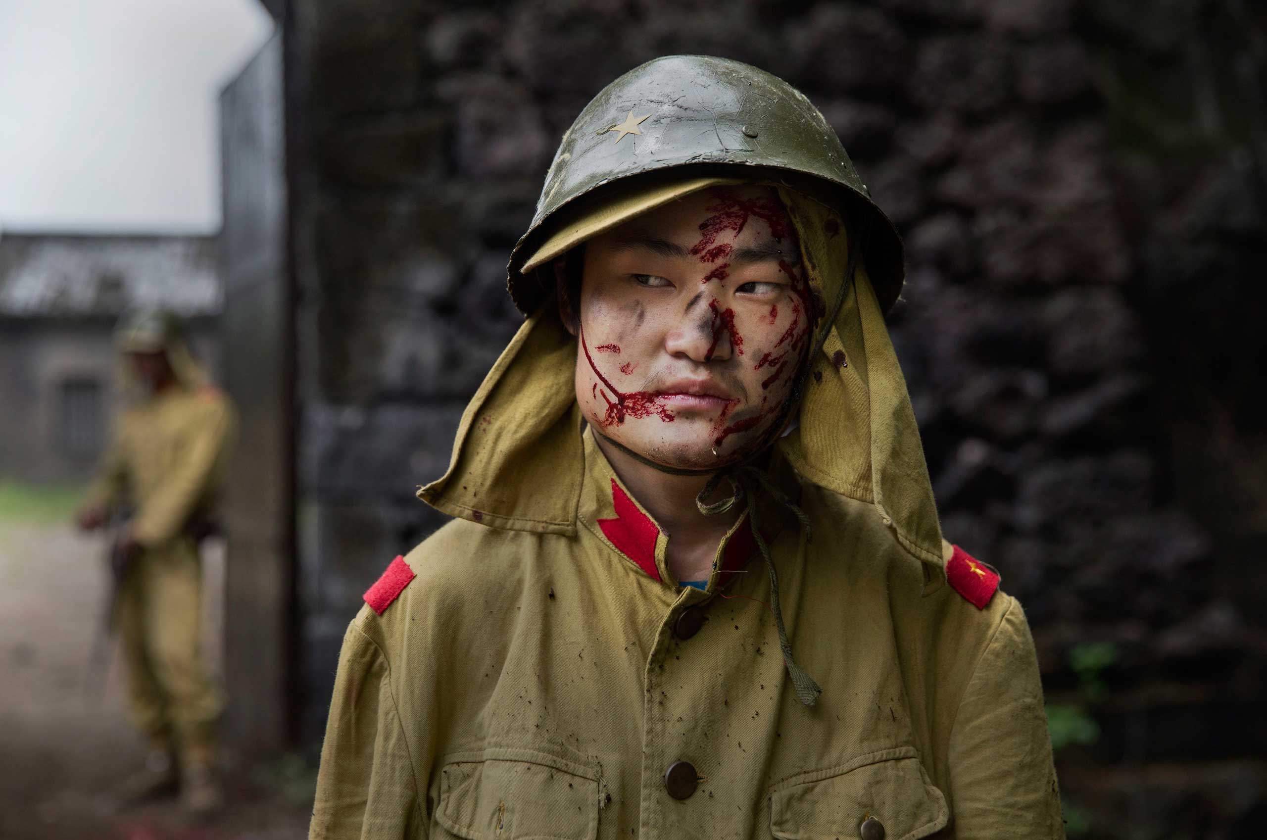 A Chinese actor playing a wounded Japanese soldier waits between scenes during the filming of the series The Last Noble, in Fangyan, on Aug. 13, 2015.