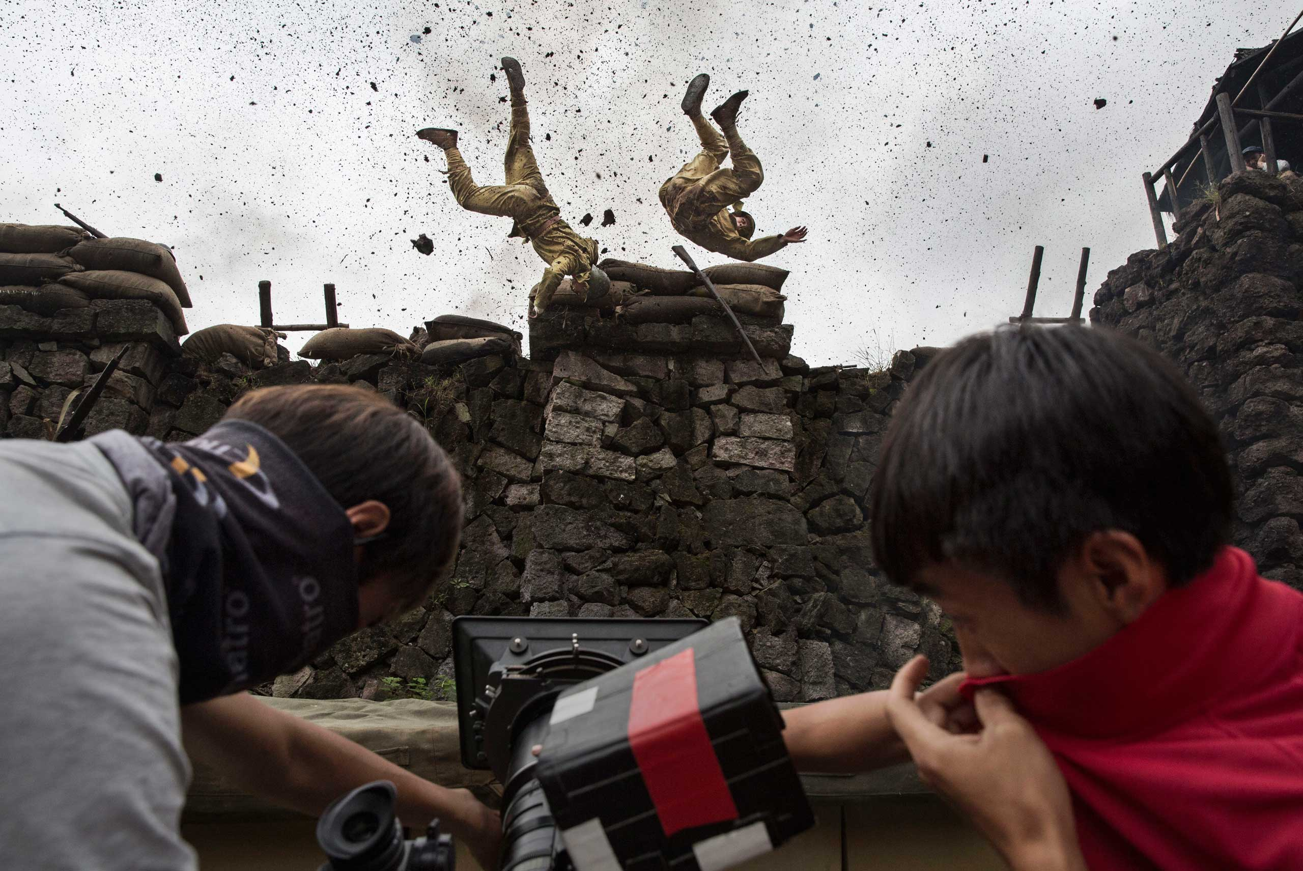 Chinese actors playing Japanese soldiers are blown off a wall in an explosion during the filming of the series The Last Noble set during the second Sino-Japanese War in Fangyan, China, on Aug. 13, 2015 .