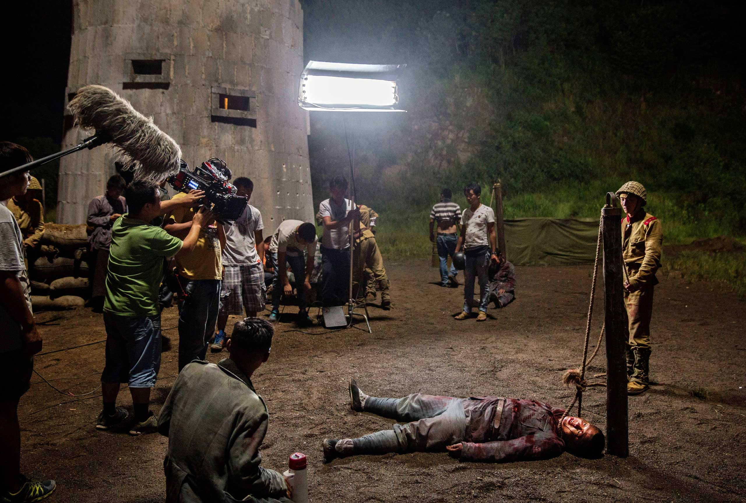 An actor playing a Nationalist soldier prisoner held by Japanese soldiers lays on the ground with a rope around his neck during filming of a series set during the second Sino-Japanese War, in Hengdian,  on Aug. 11, 2015