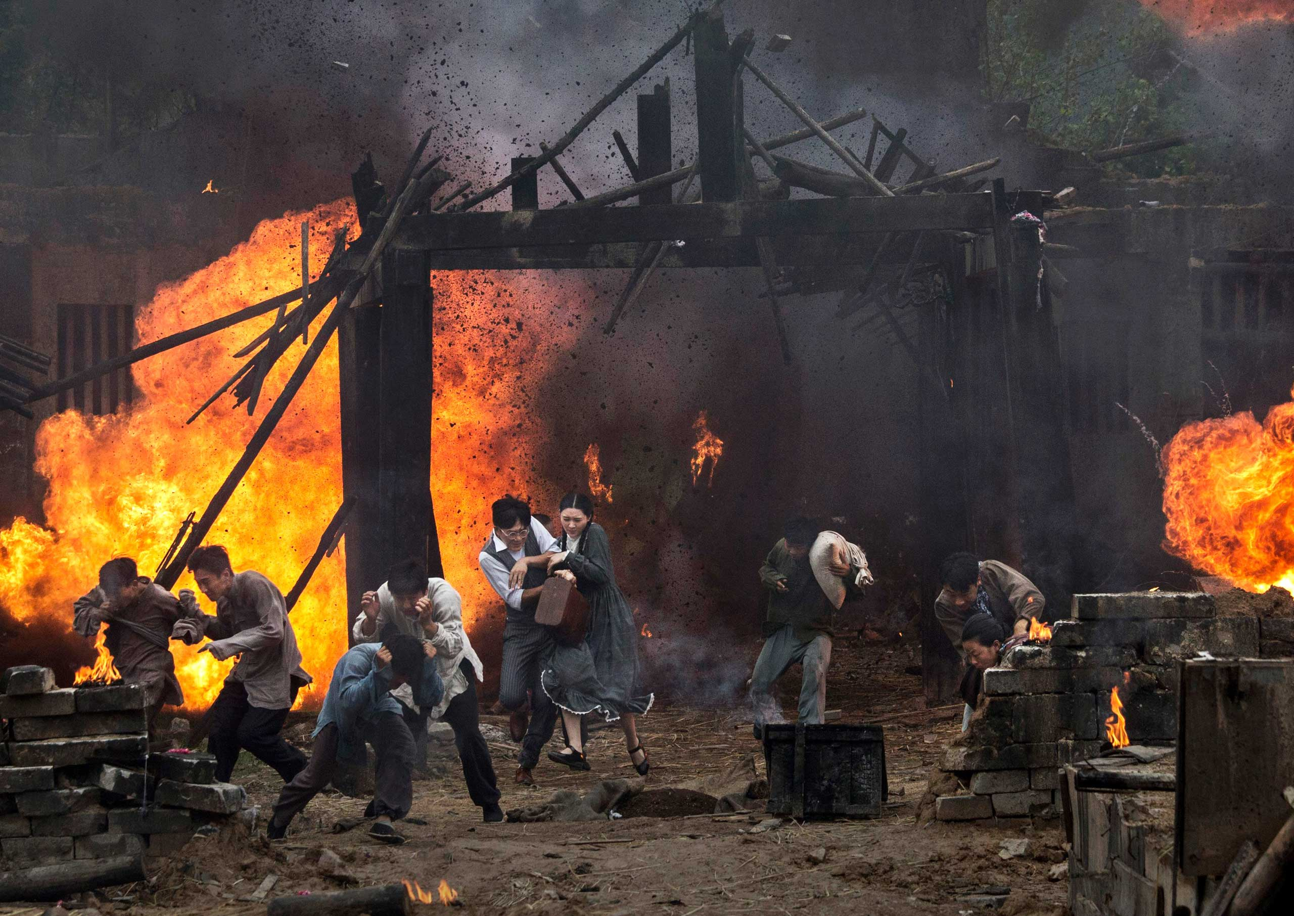 Actors playing Chinese villagers run in a battle scene during filming of the series The Nu River War, in Hengdian, on Aug. 12, 2015.