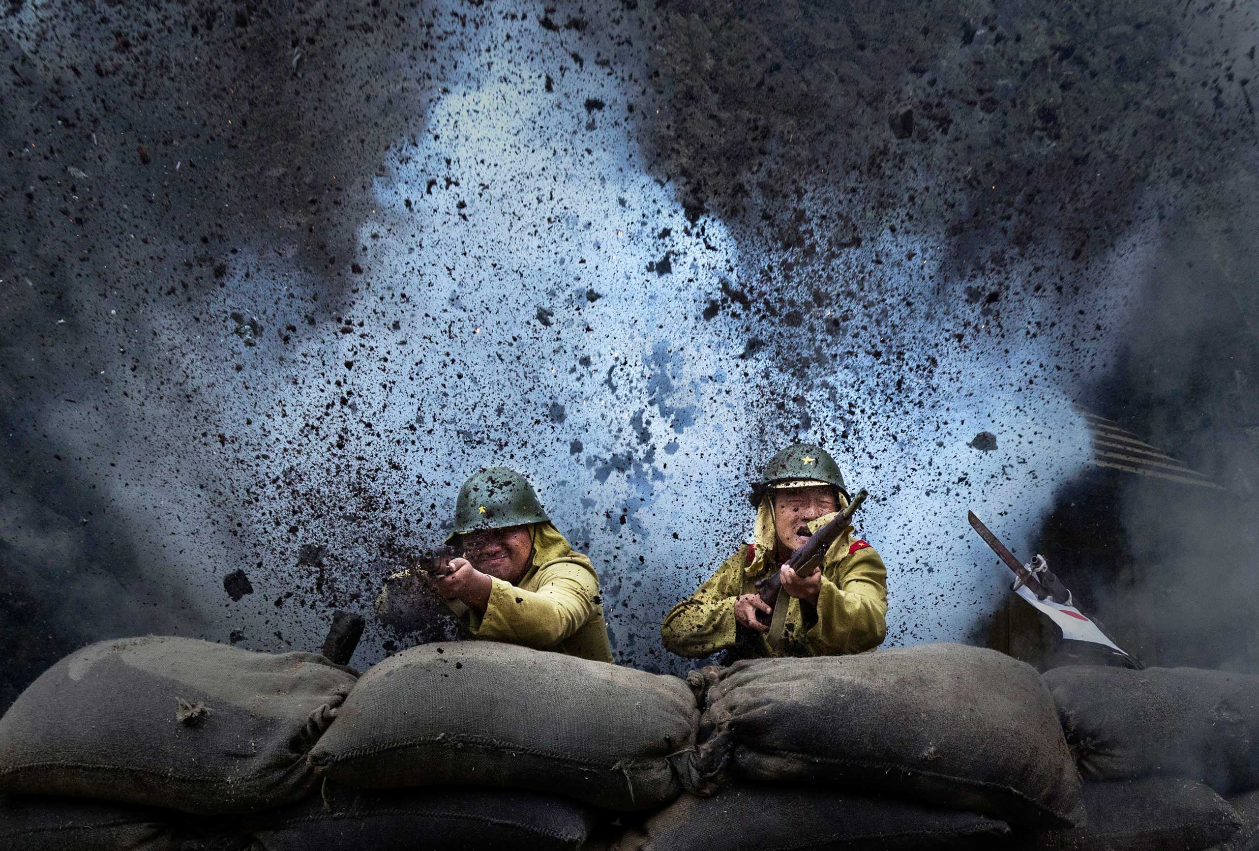 An explosion goes off as Chinese actors playing Japanese soldiers are filmed in a battle scene during filming of the series The Last Noble, in Fangyan, on Aug. 13, 2015.
