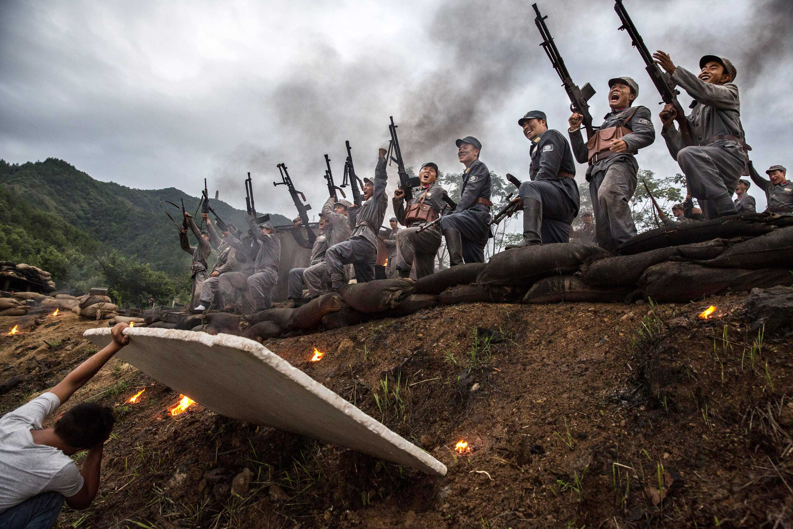Actors playing Nationalist soldiers shout as they stand above a trench during  filming of a battle segment in the series Legend of the Stupid Guy, in Hengdian, on Aug. 11, 2015.