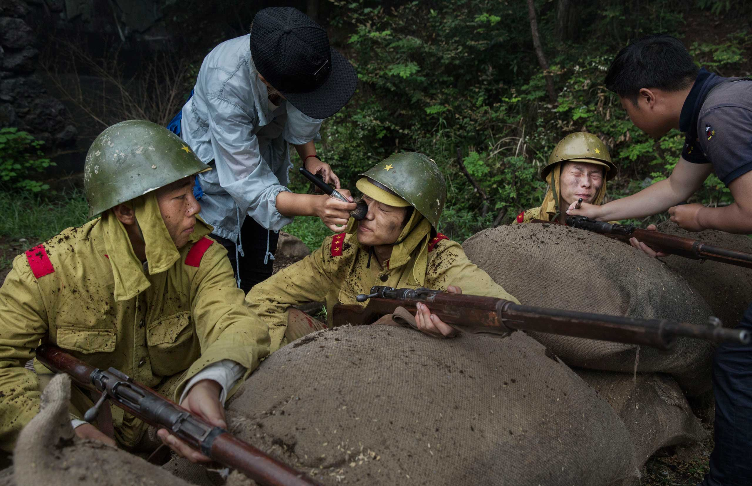 Make-up effects artists apply charcoal to Chinese actors playing Japanese soldiers during the filming in Fangyan, on Aug. 13, 2015.