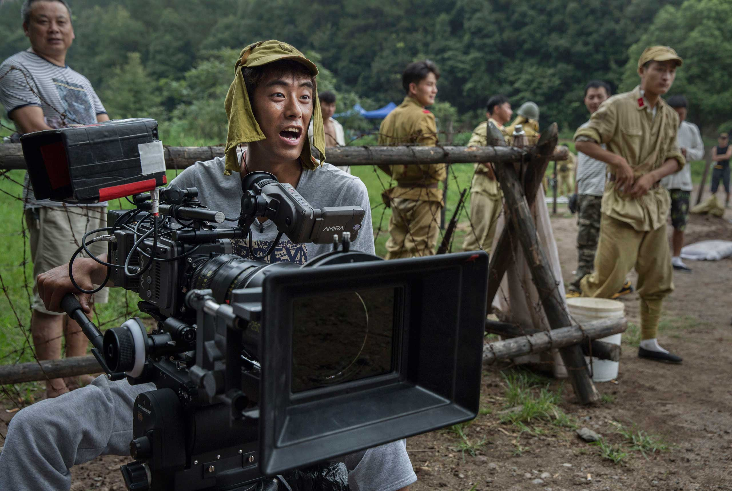 A cinematographer wears a Japanese army hat during the filming in Fangyan, on Aug. 11, 2015.