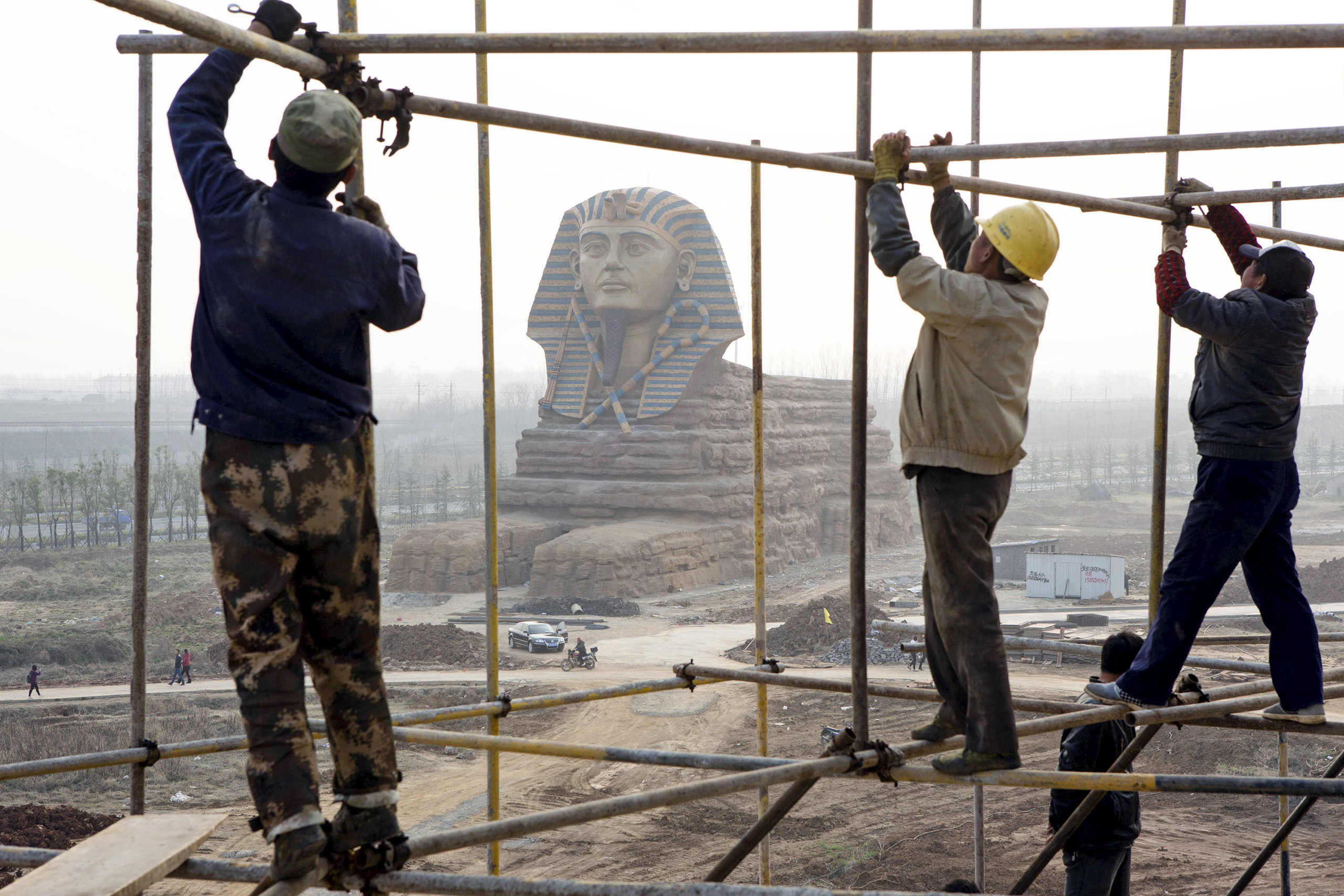 Laborers work on scaffolding near a full-scale replica of the Sphinx at an unfinished movie and animation theme park in Chuzhou, Anhui province.