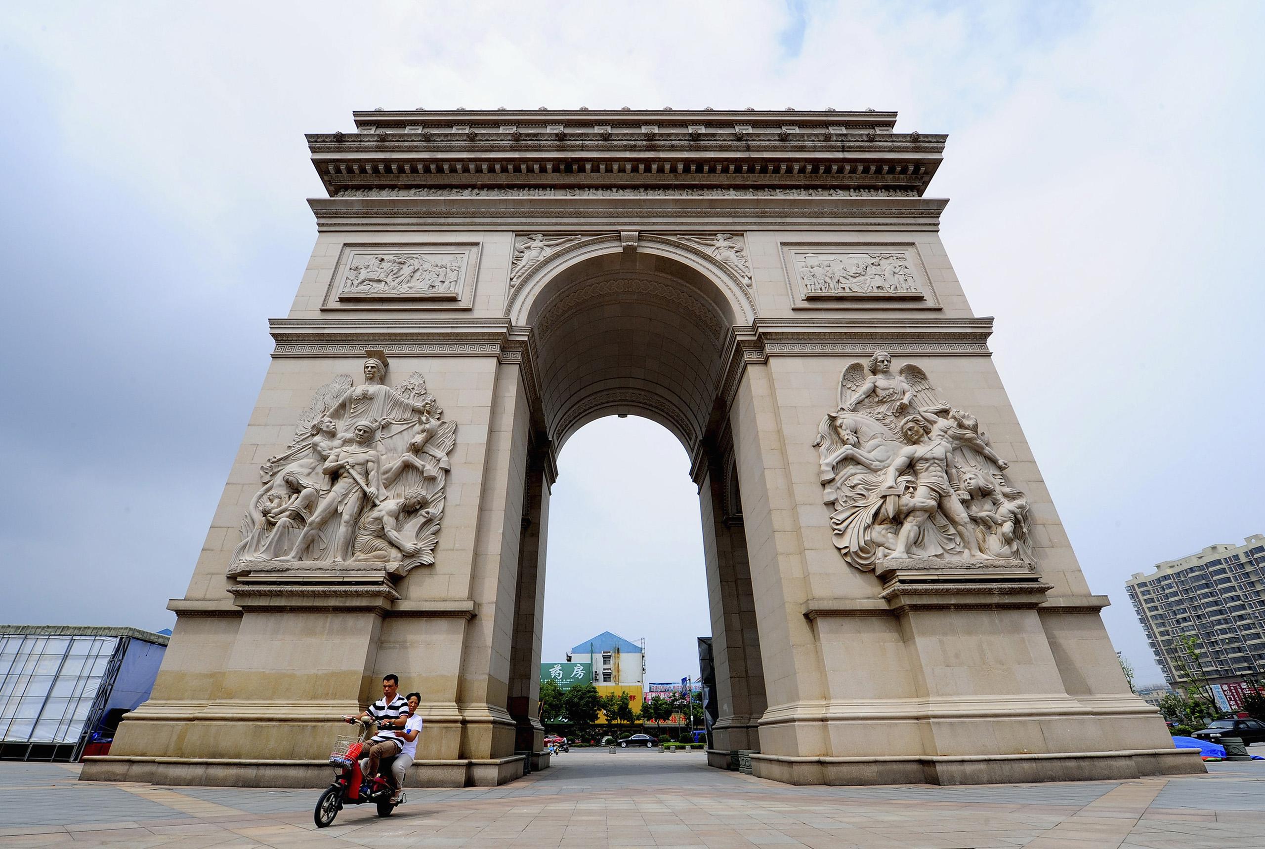 A motorcyclist rides past a 10-metre-high miniature replica of the Arc de Triomphe monument in Paris, in Jiangyan, Jiangsu province.