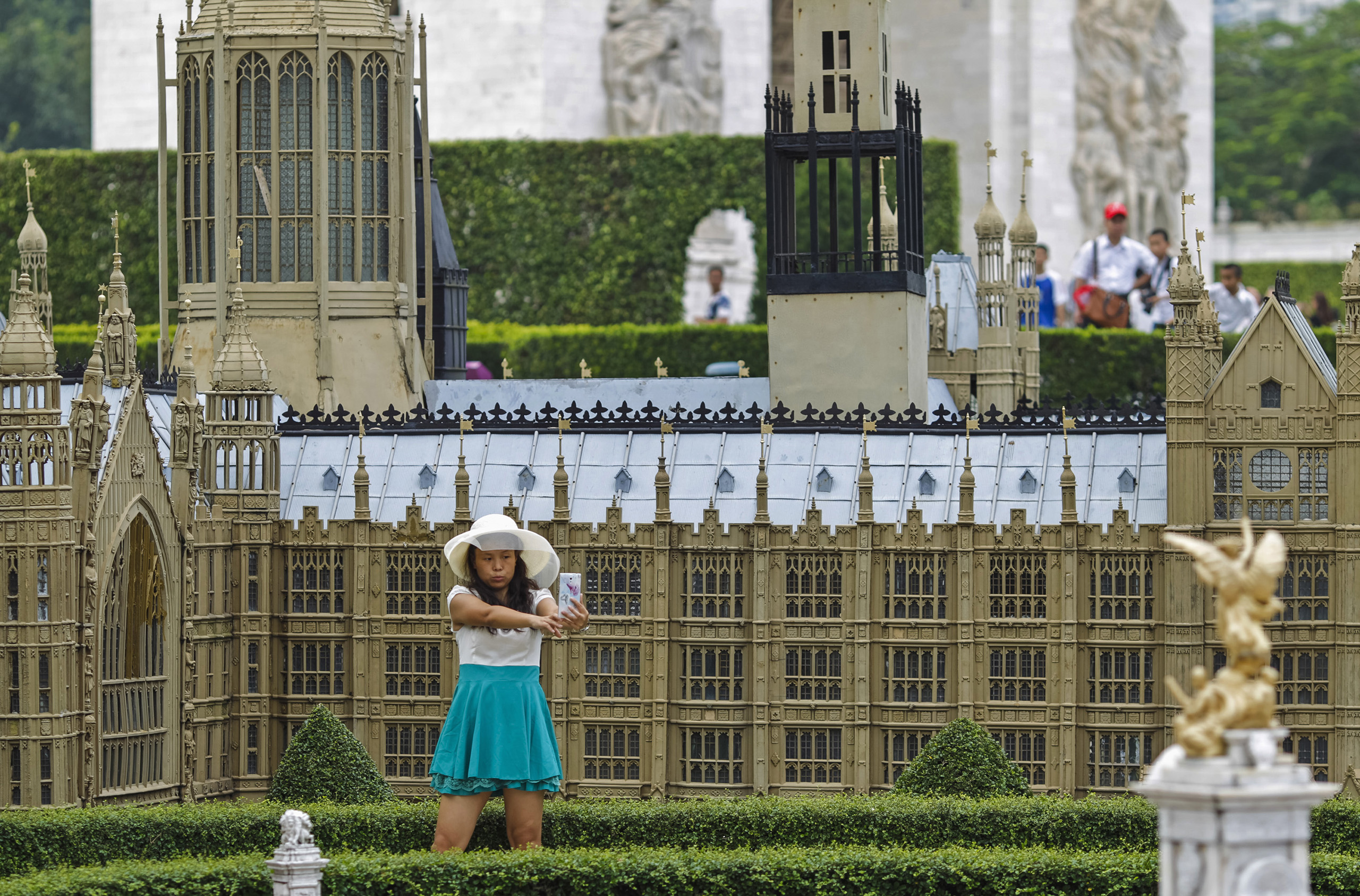 A woman poses for a selfie in front of a miniature replica of London's Houses of Parliament, at a theme park called  Window Of The World  in Shenzhen, Guangdong province.