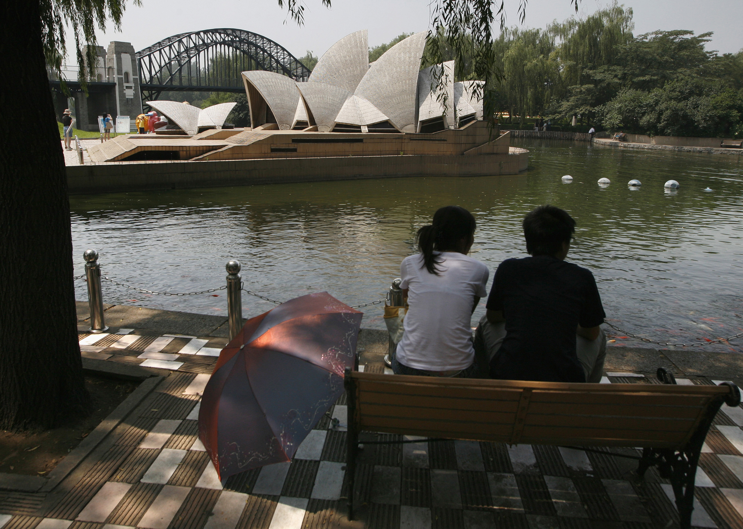 Visitors to Beijing's World Park sit in front of a replica of the Sydney Opera House and Harbour Bridge.