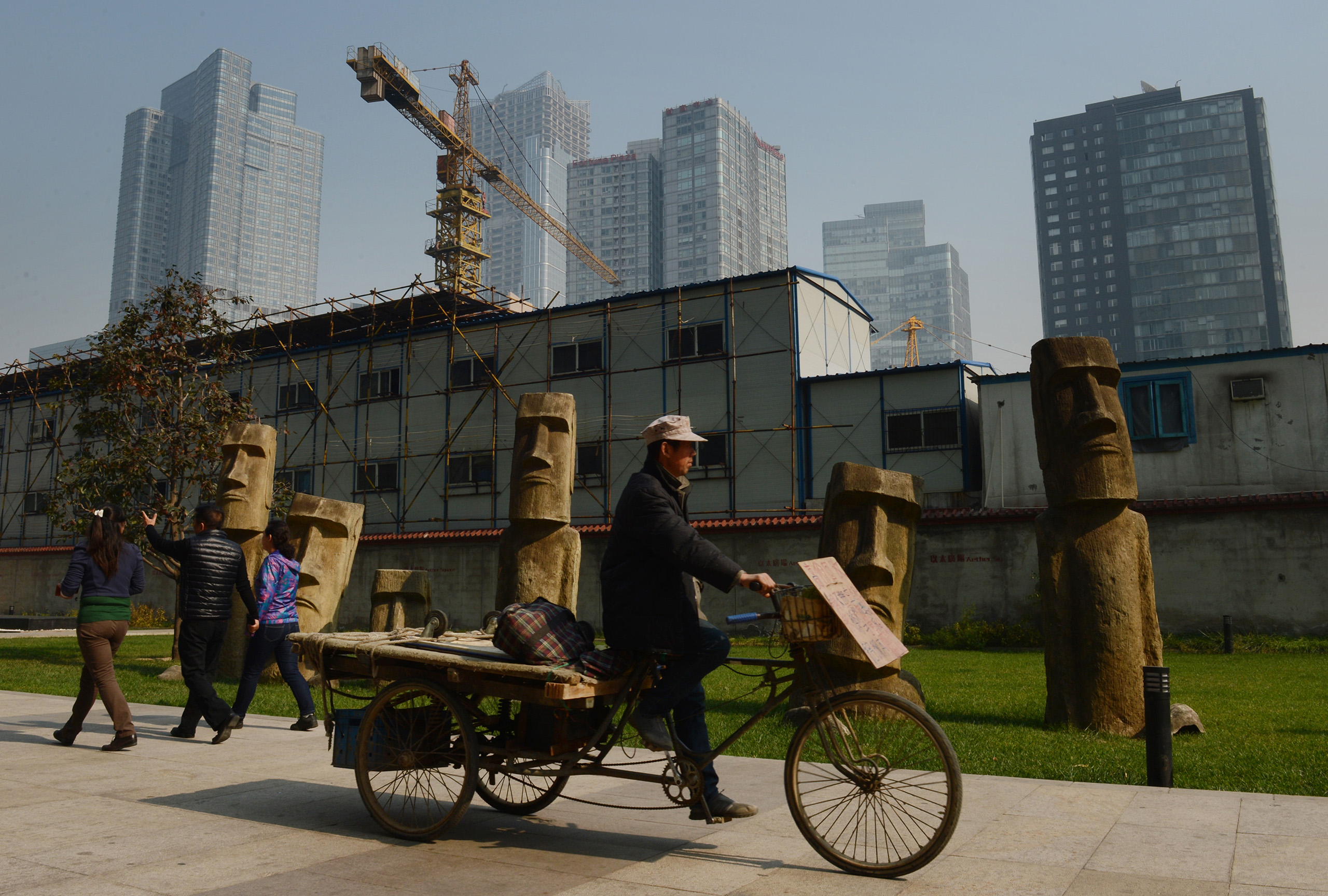 A Chinese worker rides past statues modeled on the famous Easter Island  Moai  in the Central Business District of Beijing.