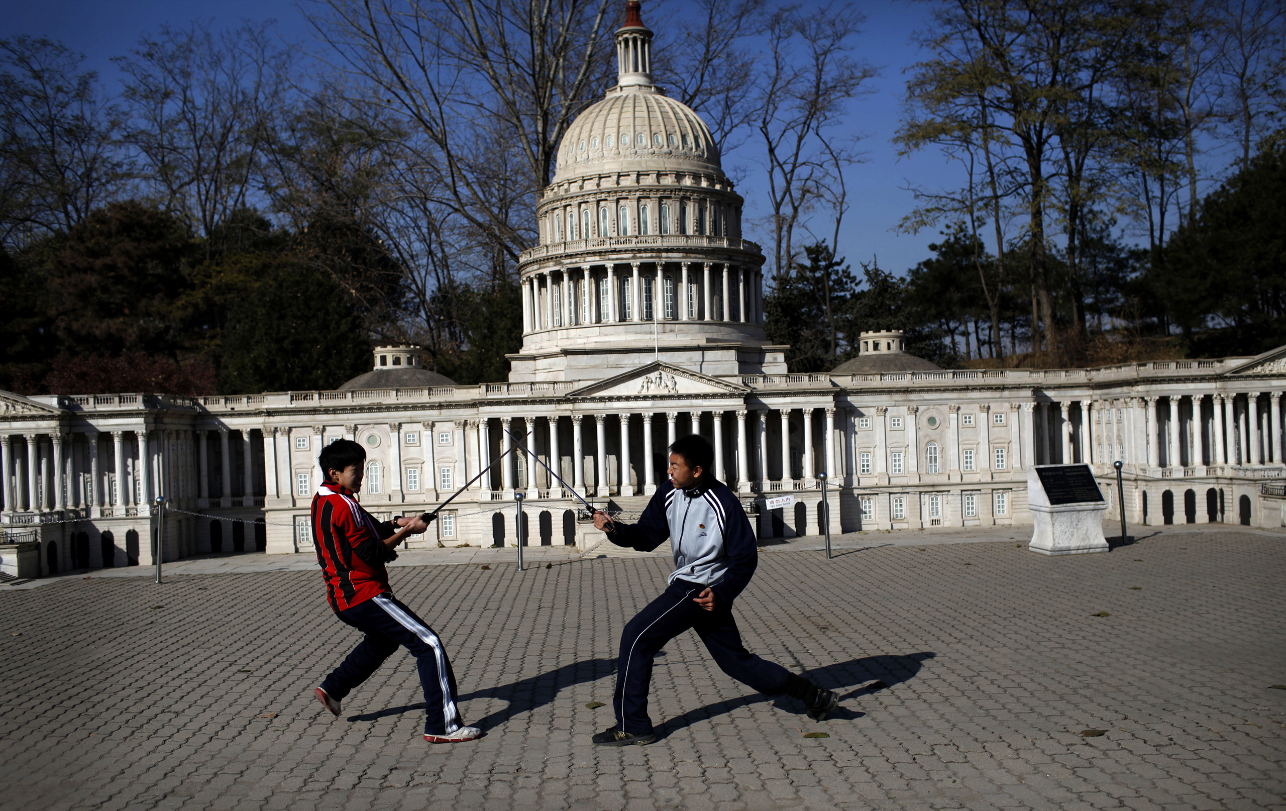 Two boys play-fight with swords in front of the mini replica of the United States Capitol in Beijing World Park.