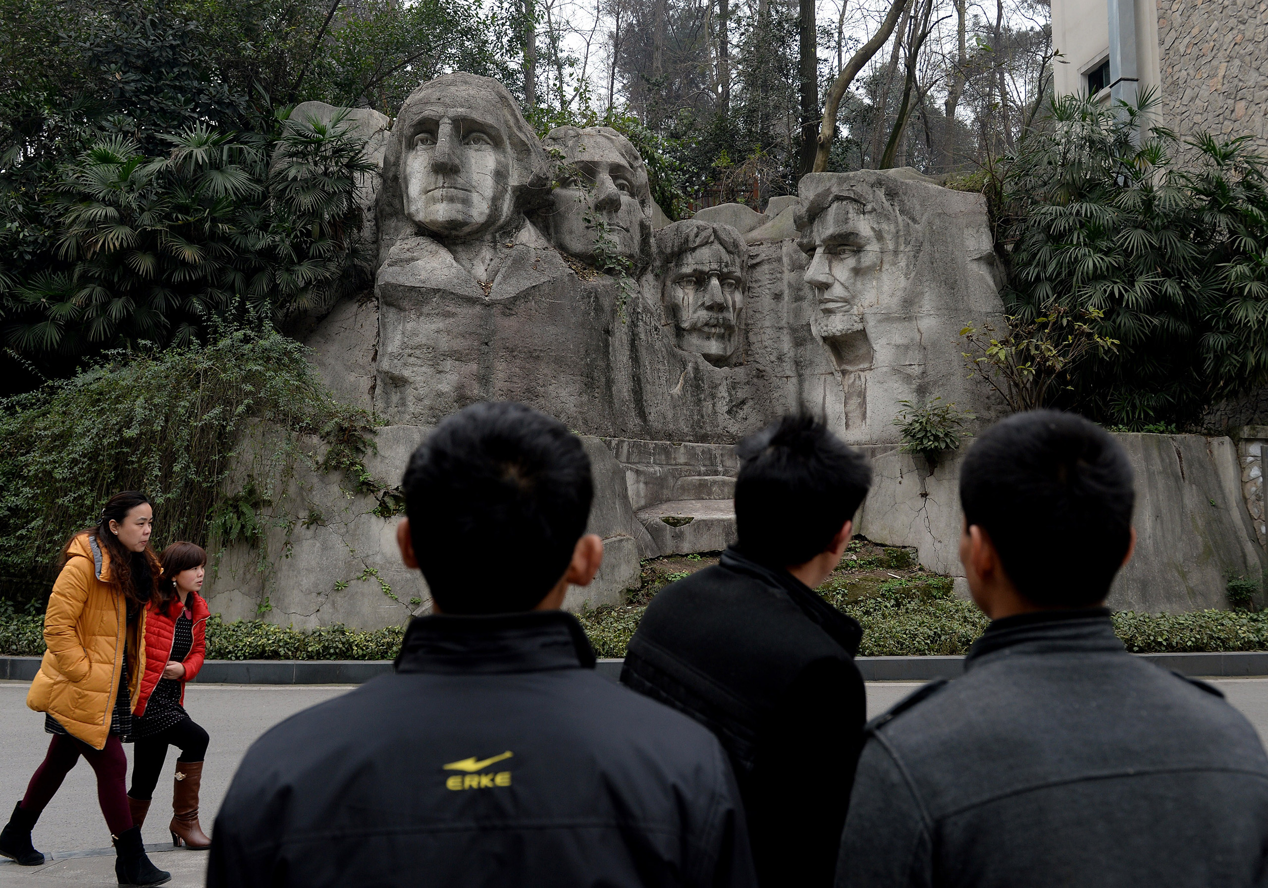 Visitors walk past a copy of Mount Rushmore at a park in Chongqing.