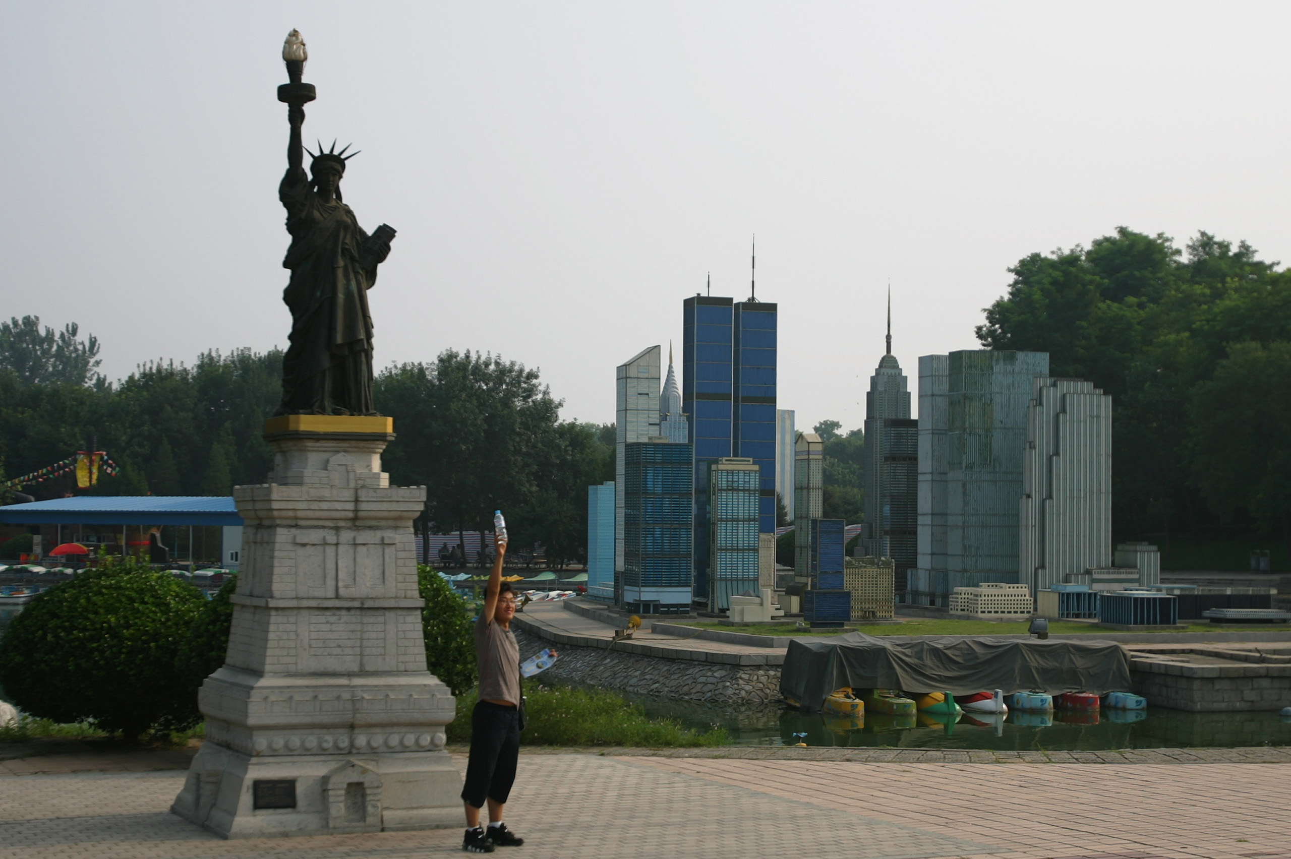 A man holds up a water bottle to mimic a replica of the Statue of Liberty near replicas of the New York skyline at the World Park in Beijing.