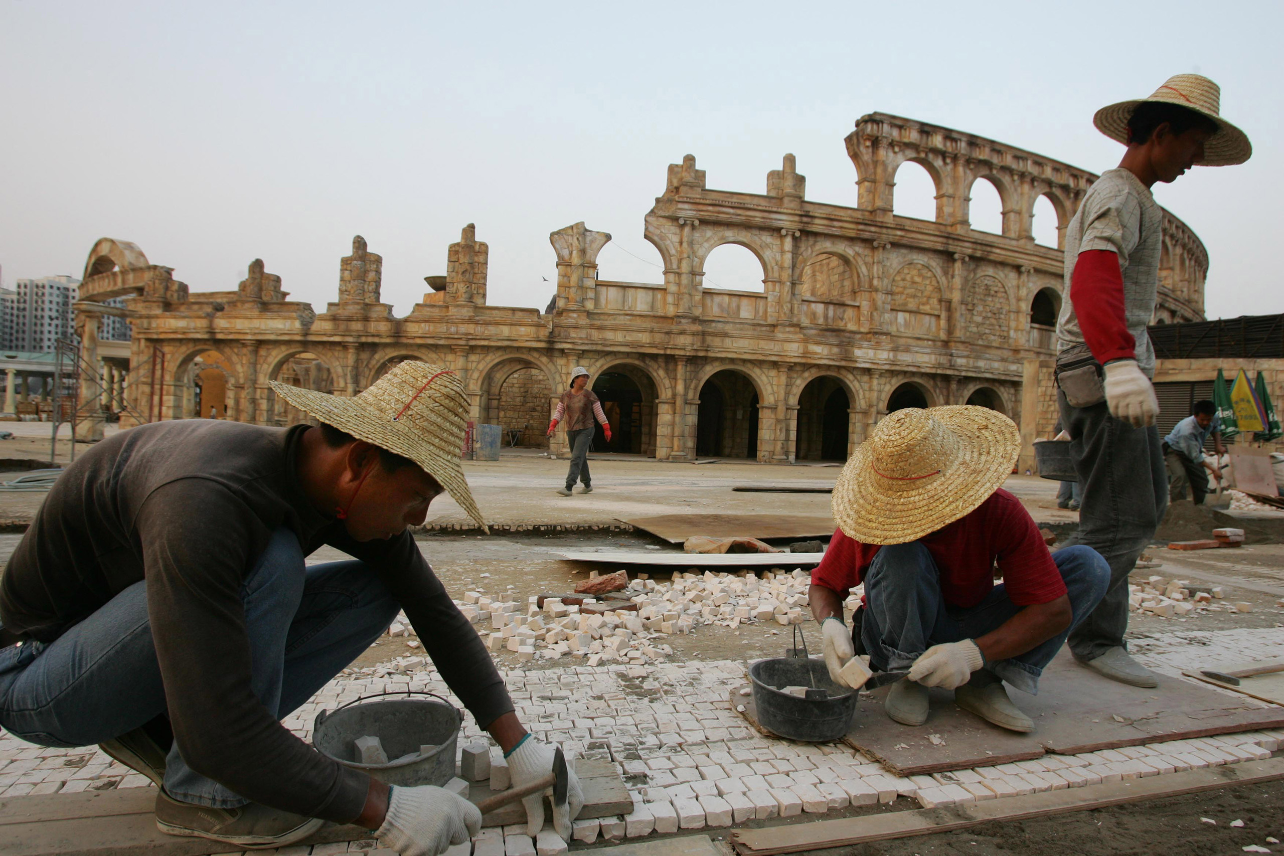 Workers build pavement outside a replica of the Roman Colosseum at Fisherman's Wharf in Macau.