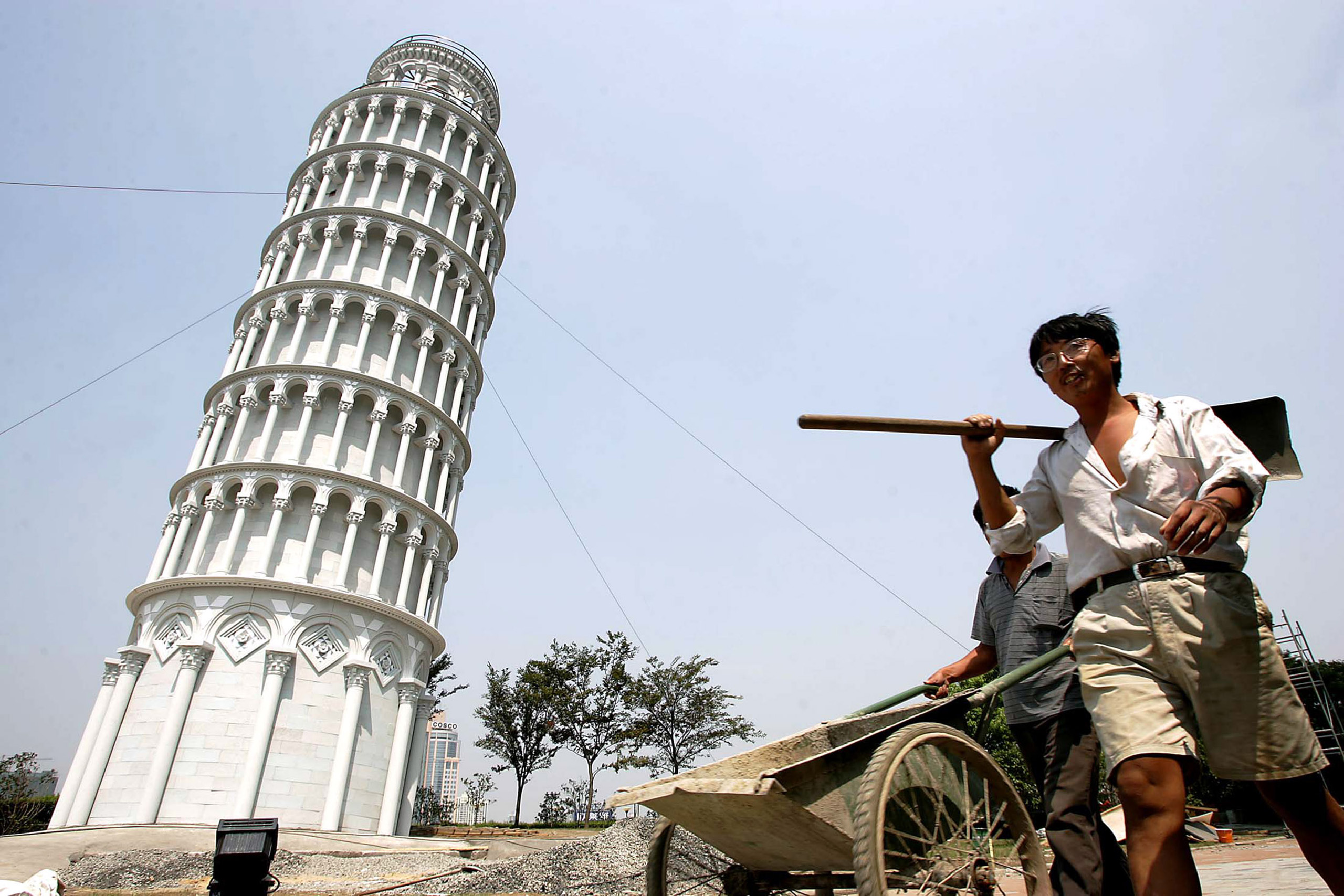 Chinese workers walk past a 1:4 scale mini leaning tower of Pisa in Shanghai.