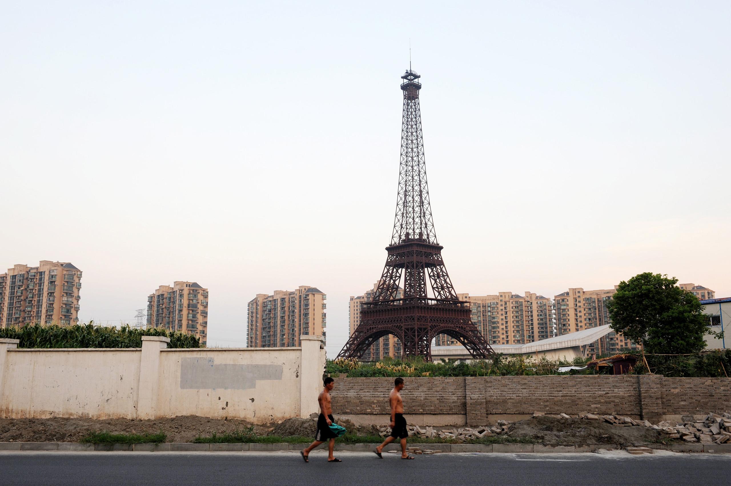 Pedestrians walk past a half-sized replica of the Eiffel Tower at Tianducheng, a small Chinese community built to imitate Paris, in Hangzhou city, Zhejiang province.