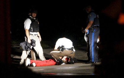 A black man lies badly wounded with blood on his shirt after a police officer involved shooting in Ferguson