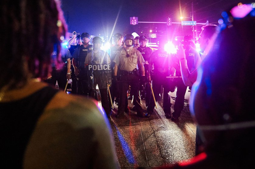 St. Louis County Police and Missouri State Highway Patrol troopers (C) stand guard as protesters (foreground) march on West Florissant Avenue in Ferguson, Missouri on August 9, 2015. A day of peaceful remembrance marking the anniversary of 18-year-old black teen Michael Brown's killing by police in the US city of Ferguson came to a violent end on August 9 as gunfire left at least one protester injured. AFP PHOTO / MICHAEL B. THOMASMichael B. Thomas/AFP/Getty Images