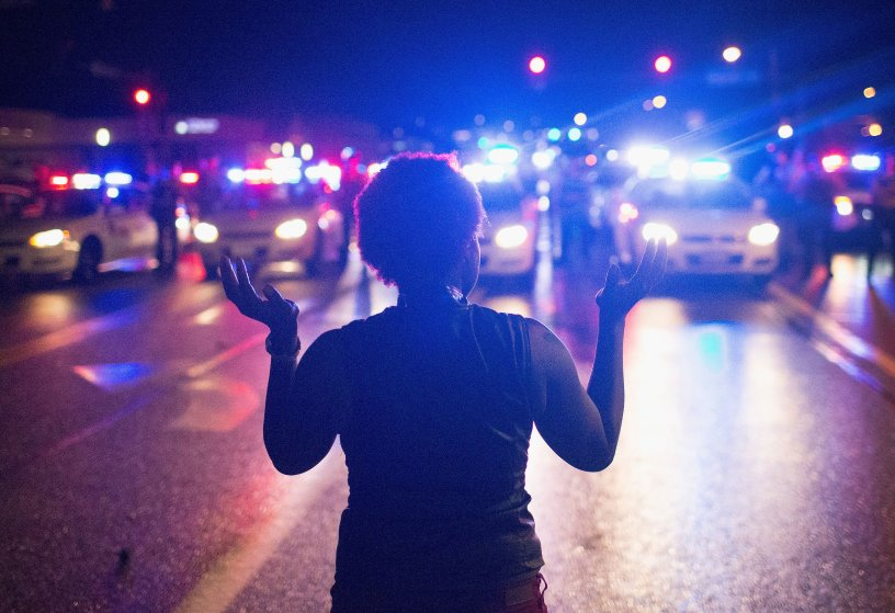 FERGUSON, MO - AUGUST 09: Demonstrators, marking the one-year anniversary of the shooting of Michael Brown, face off with police during a protest along West Florrisant Street on August 9, 2015 in Ferguson, Missouri. There are reports that two people were shot when gun fire broke out during protests later in the evening. Brown was shot and killed by a Ferguson police officer on August 9, 2014. His death sparked months of sometimes violent protests in Ferguson and drew nationwide focus on police treatment of black offenders. (Photo by Scott Olson/Getty Images)