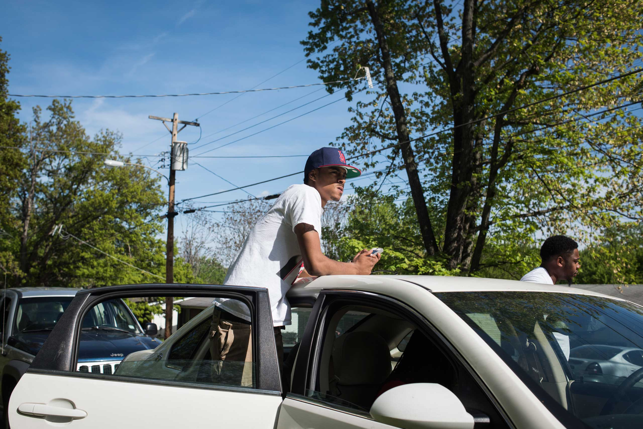 Tee Jay Banks surveys the street while hanging out with friends in the Bermuda neighborhood of Ferguson, Mo. Banks, stopped attending college because of high costs but was hoping to save up money to return to school.