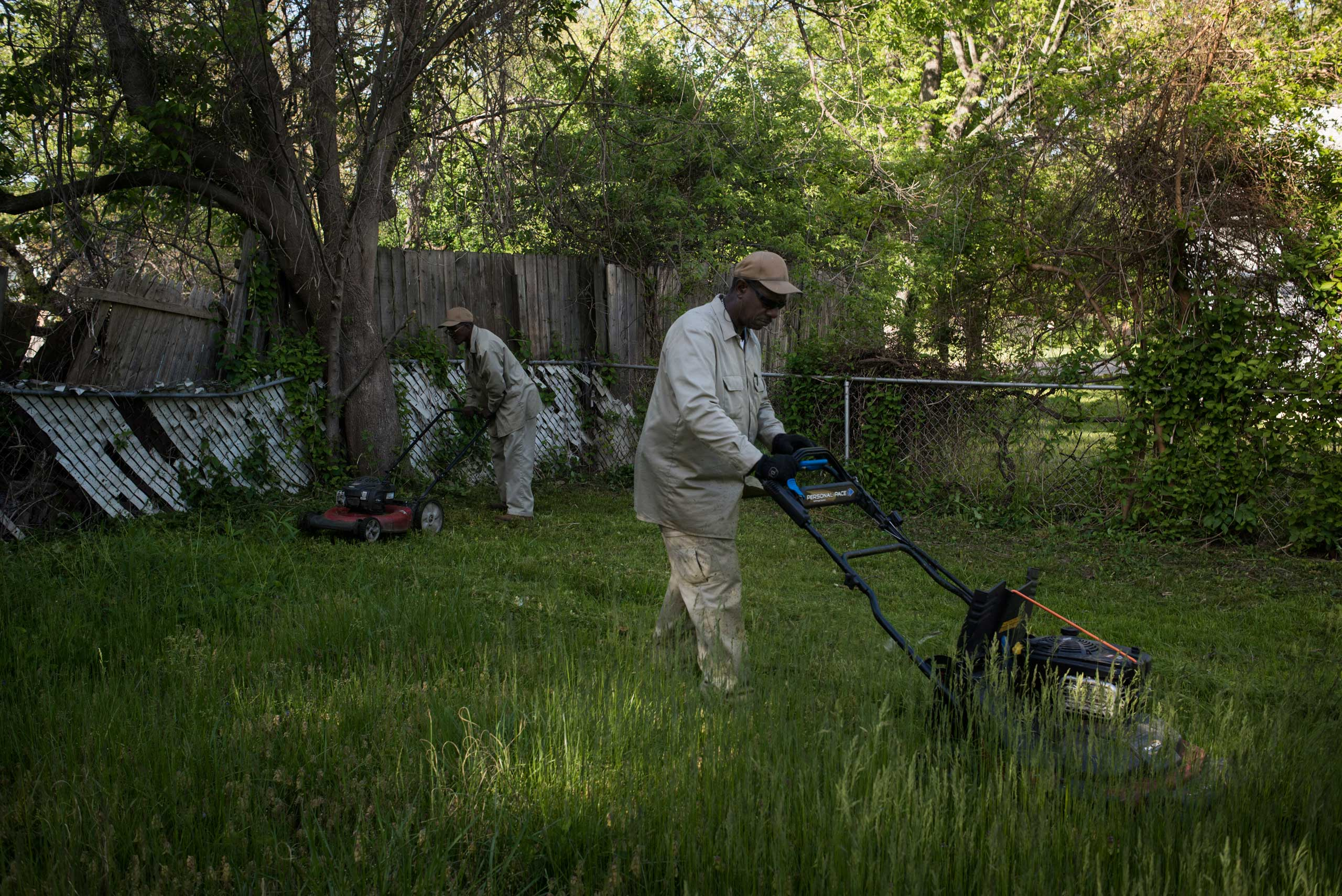 "Richard, right, clears an overgrown yard of a rental house in the Bermuda neighborhood of Ferguson, Mo. Code enforcement officers are a common sight in the neighborhood and ticket people for long lawns and many discretionary violations like ""disturbing the peace."" Code enforcement accounted for $2.46 million dollars of the city's budget in 2013."