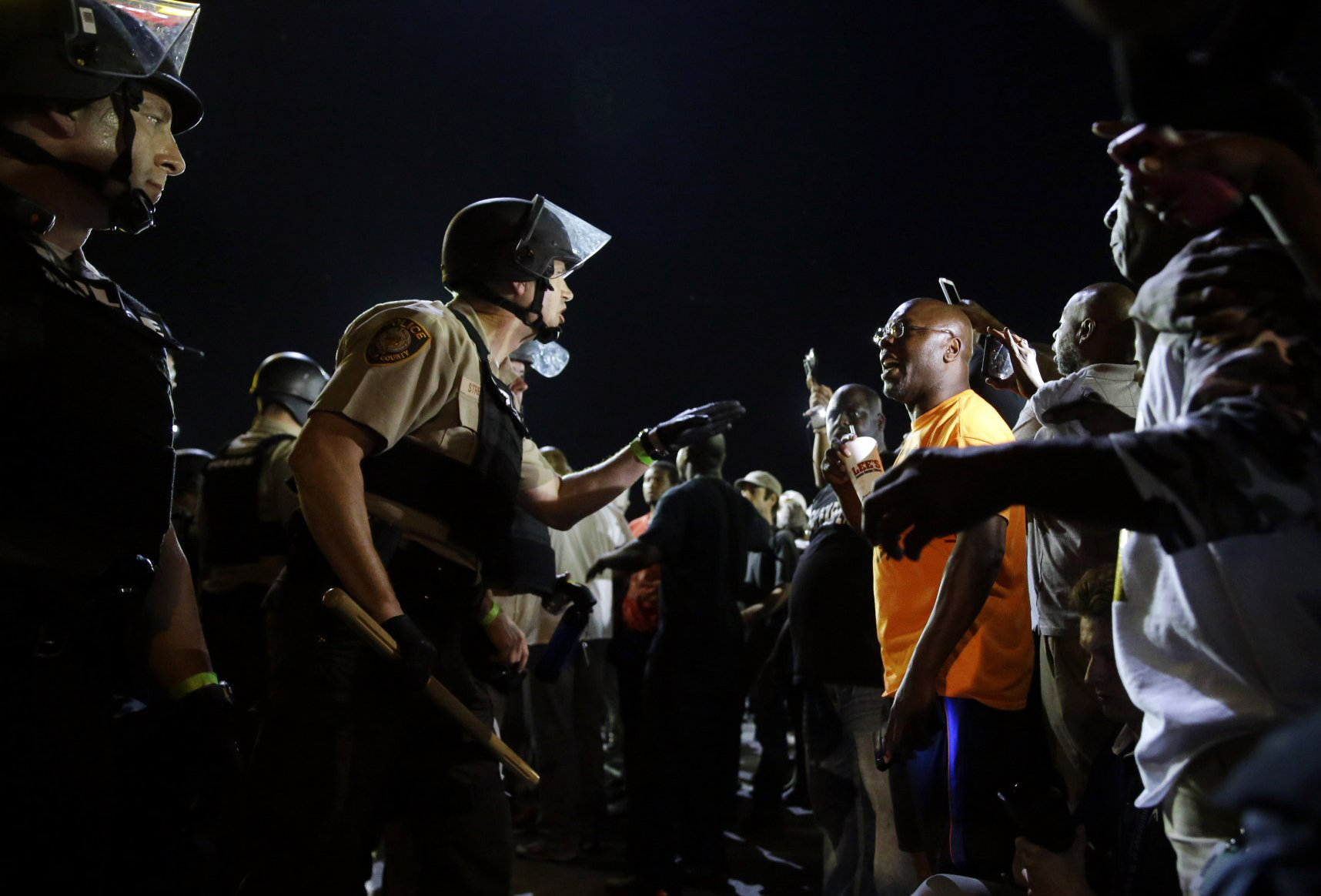 Officers and protesters face off along West Florissant Avenue on Aug. 10, 2015, in Ferguson, Mo.