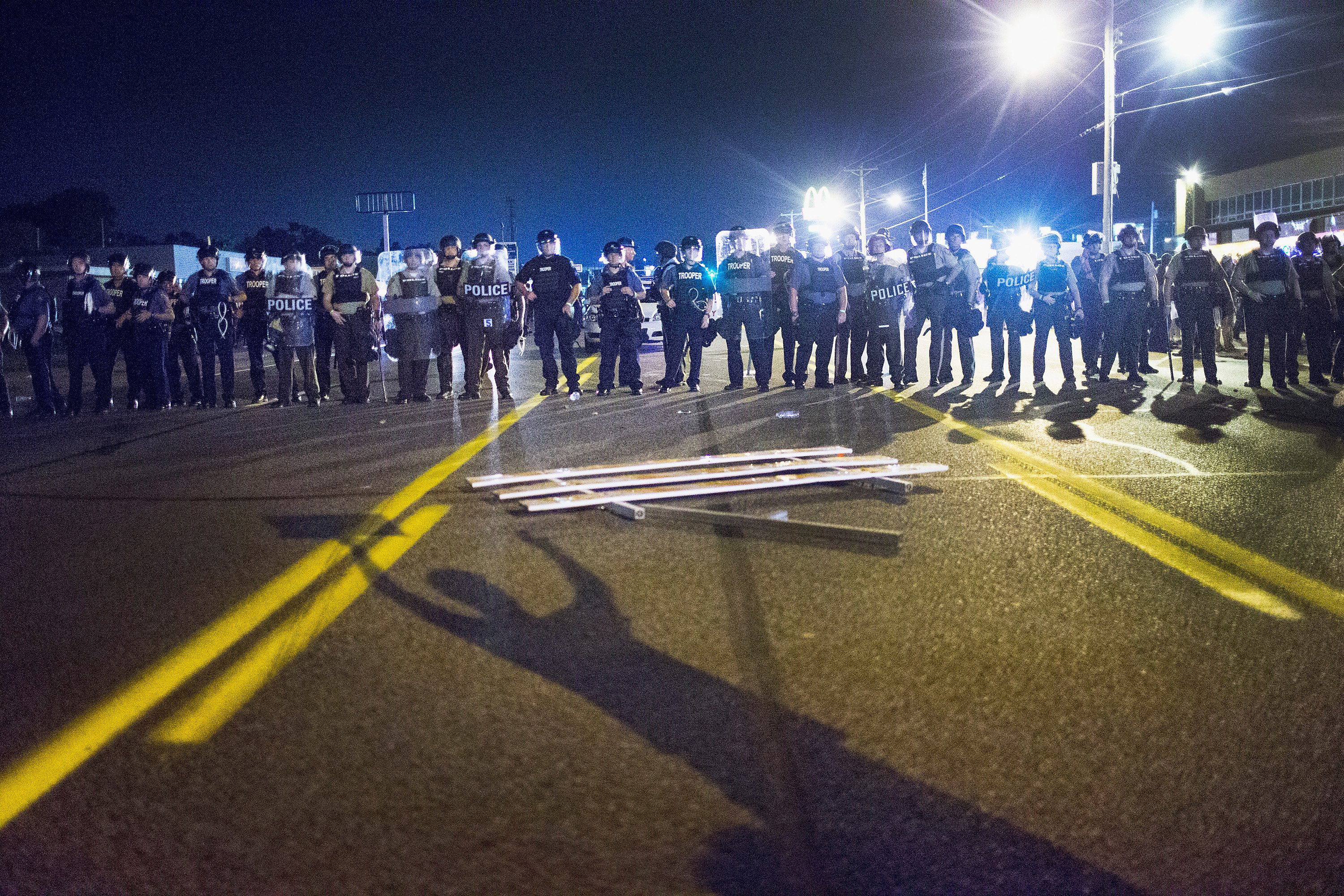 Police stand guard as demonstrators, marking the one-year anniversary of the shooting of Michael Brown, protest along West Florrisant Street on Aug. 10, 2015 in Ferguson, Mo.