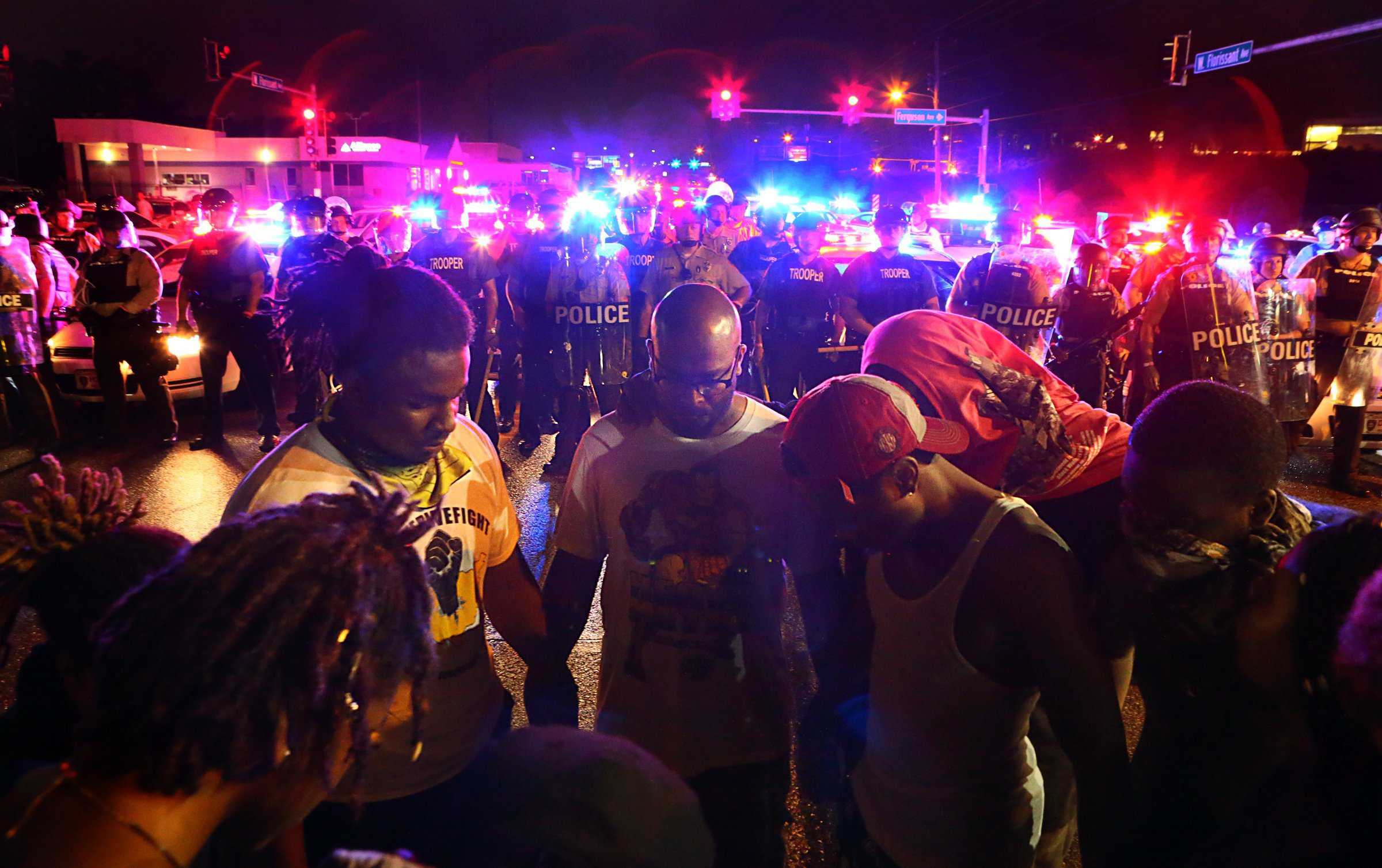 Protesters pray before confronting St. Louis County police officers lined up on West Florissant Avenue, on the anniversary of the police shooting of Michael Brown, in Ferguson, Mo. on Aug. 9, 2015.