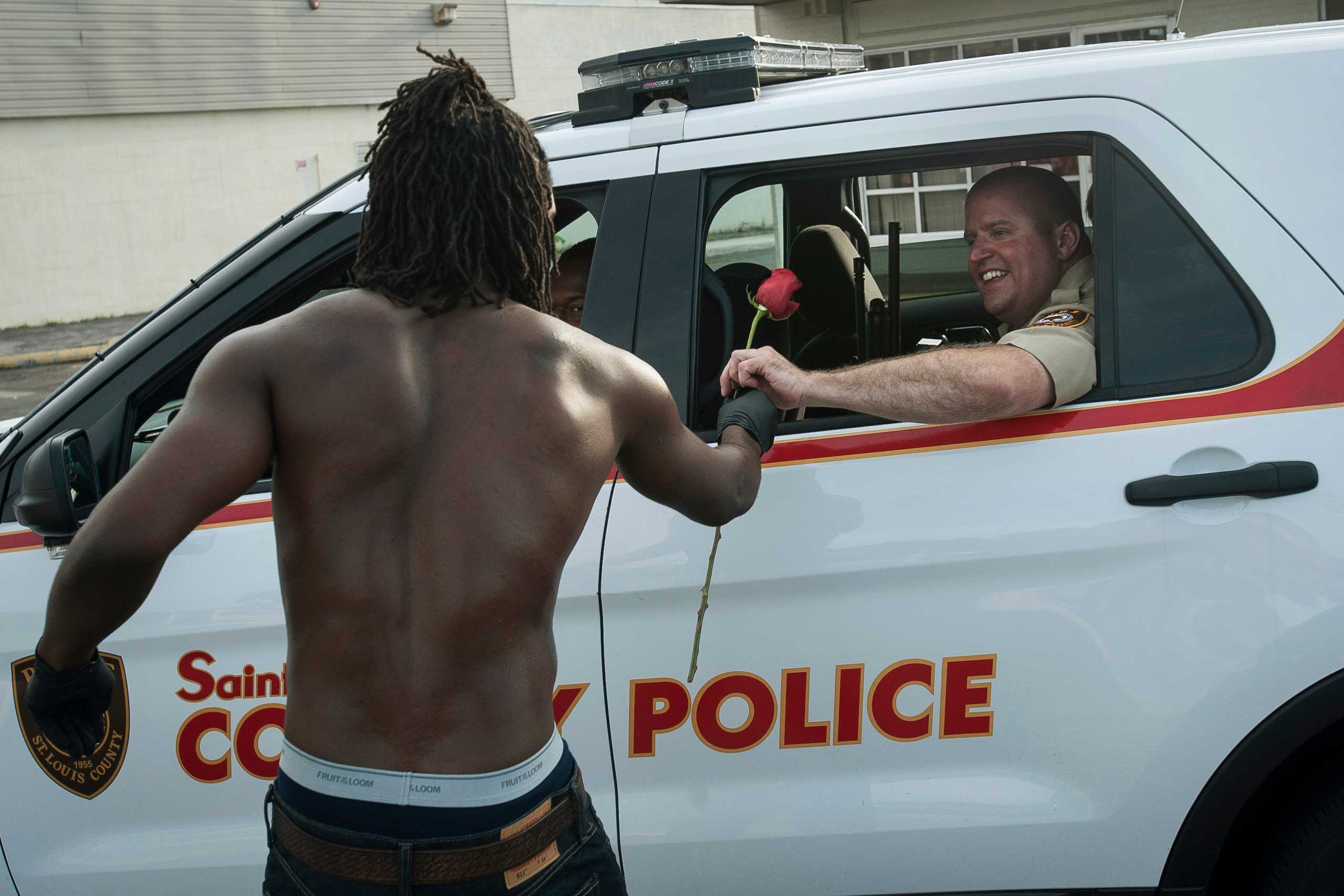 Resident John West hands a rose to a police officer during cleanup efforts in Ferguson, Mo. on Aug. 19, 2014.