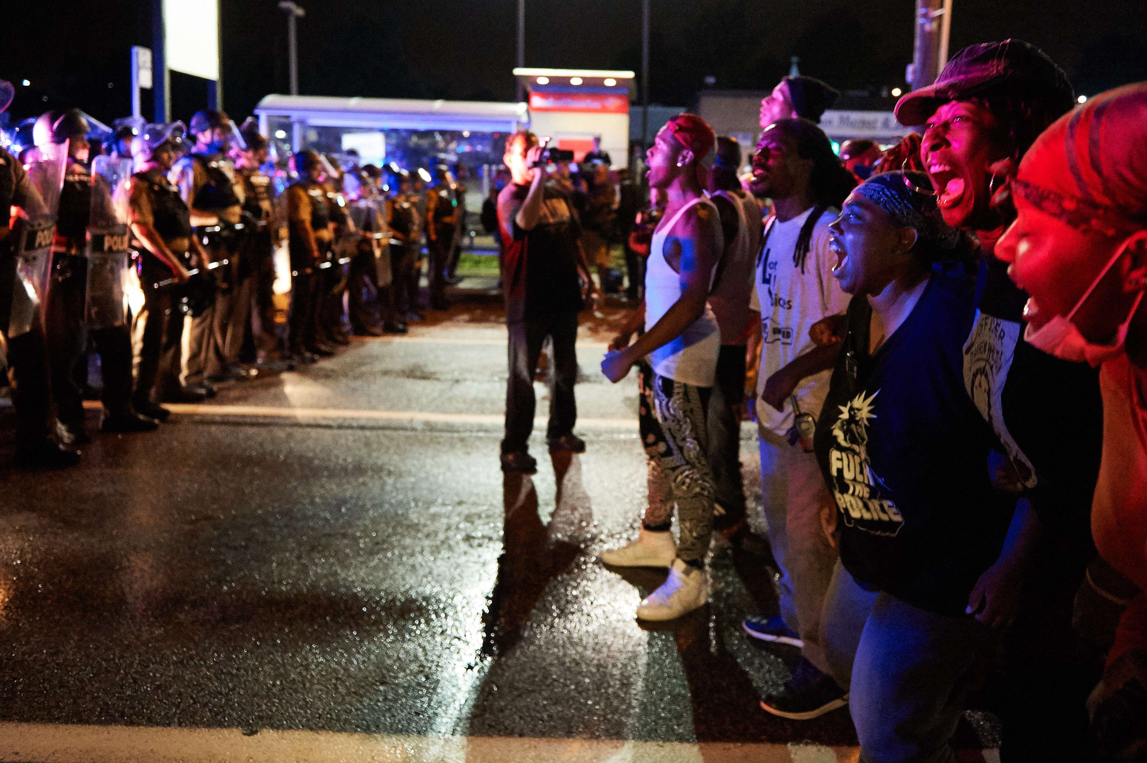 A group of demonstrators yell in front of police officers during a protest march on West Florissant Avenue in Ferguson, Mo. on August 9, 2015.