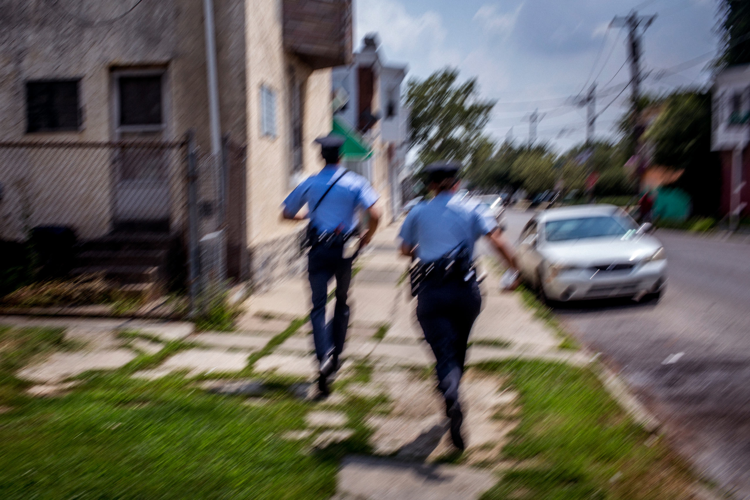First year  foot beat  officers Jonathan Dedos (left) and Ashley Sipos (right) run down the street in West Philadelphia after a radio call comes in announcing that someone has been shot in a nearby housing complex. July 28, 2015. Philadelphia, Pa.