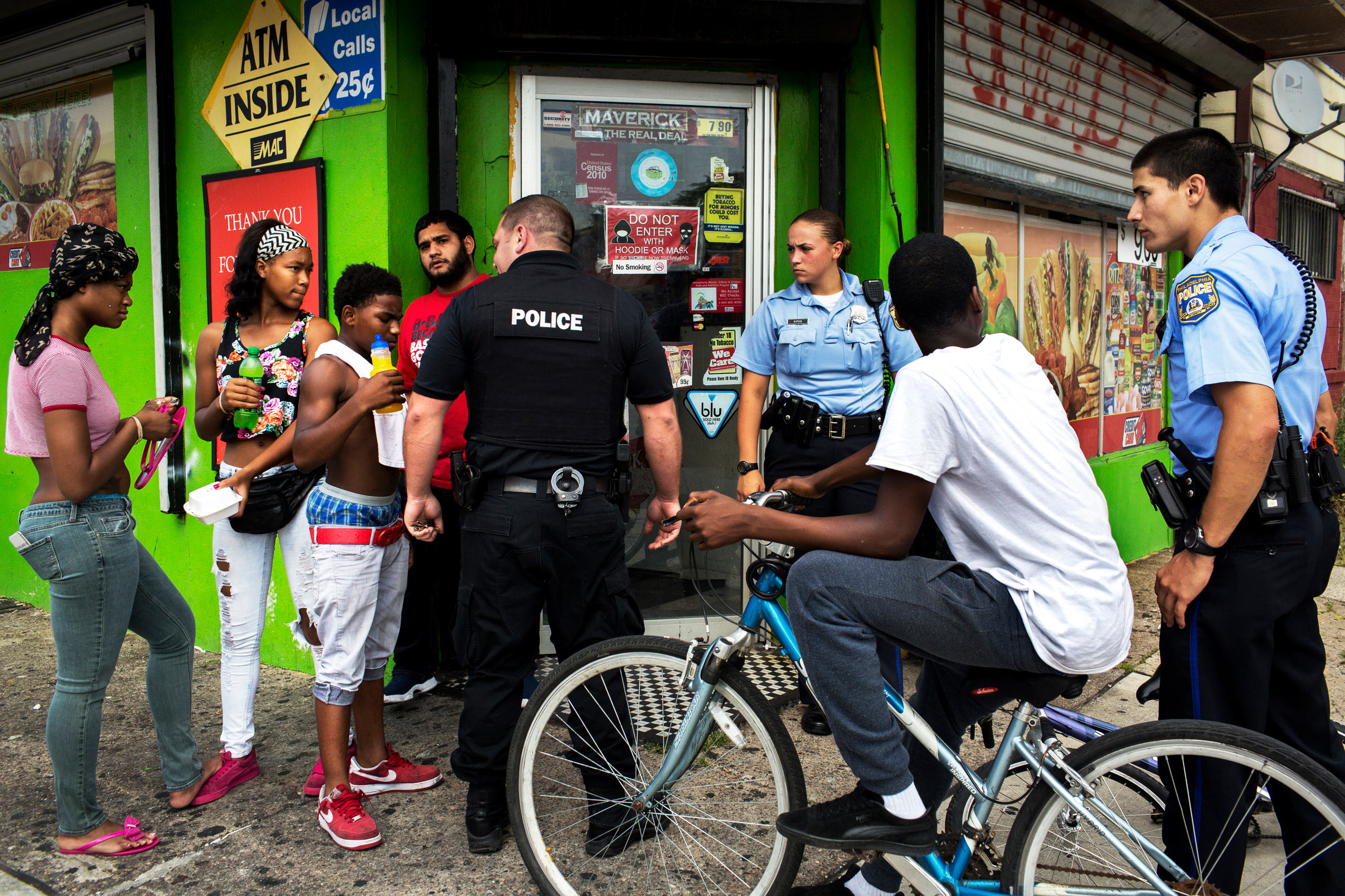 After a shooting nearby with reports of a suspect fleeing on a bicycle, officer Ryan Mundrick (center, black clothes) joins  foot beats  Ashley Sipos (center right) and Jonathan Dedos (right) in questioning a group of youths as they come out of a bodega. Dispatch had sent out information that there was a black male suspect on a bicycle, so police fanned out looking for people of that description, including many of the youths in the neighborhood. After a brief interaction the police and youth went their separate ways without incident.                                July 28, 2015. Philadelphia, Pa.