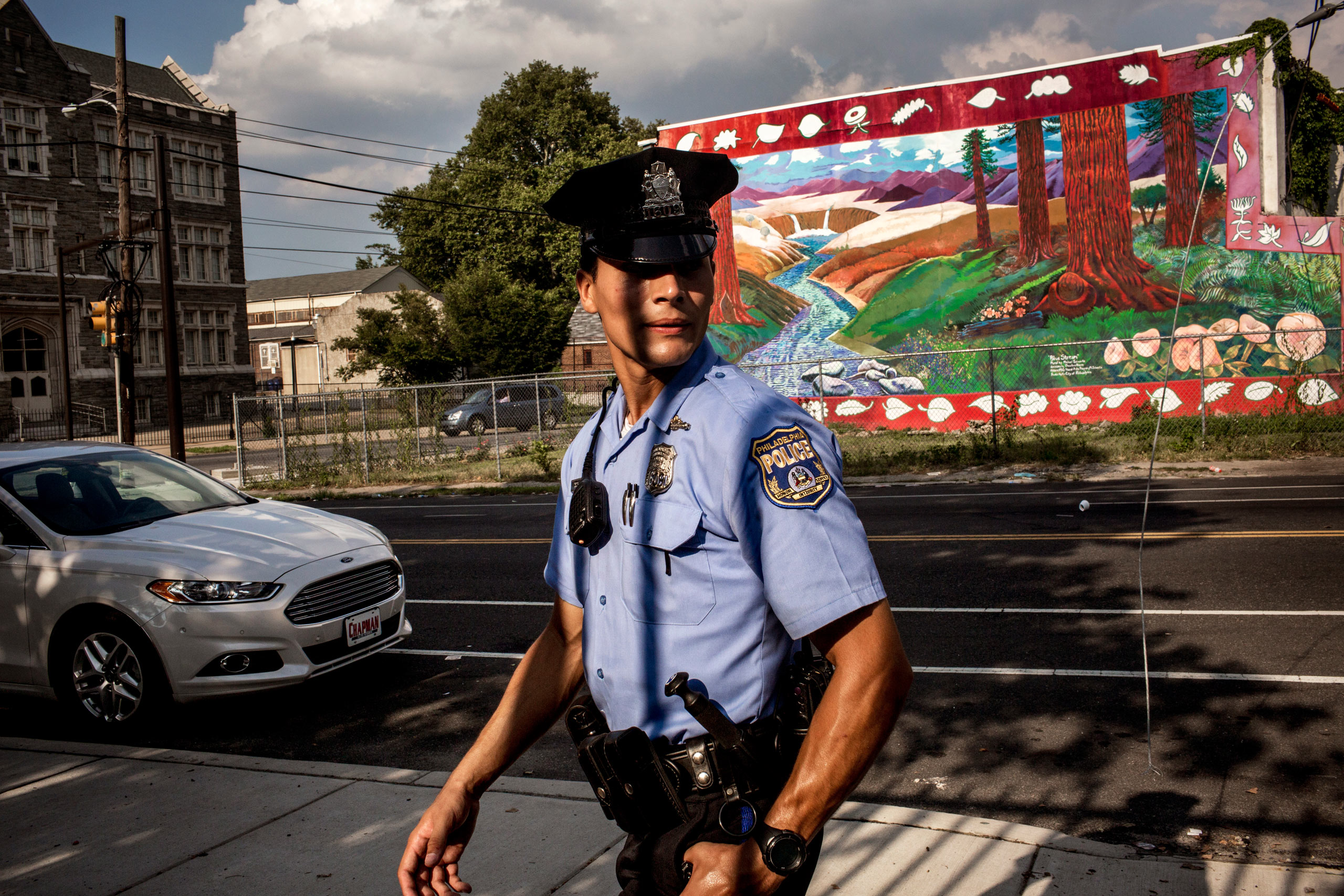 First year officer Jonathan Dedos (a  foot beat ) walks his beat, searching for a shooting suspect. July 28, 2015. Philadelphia, Pa.