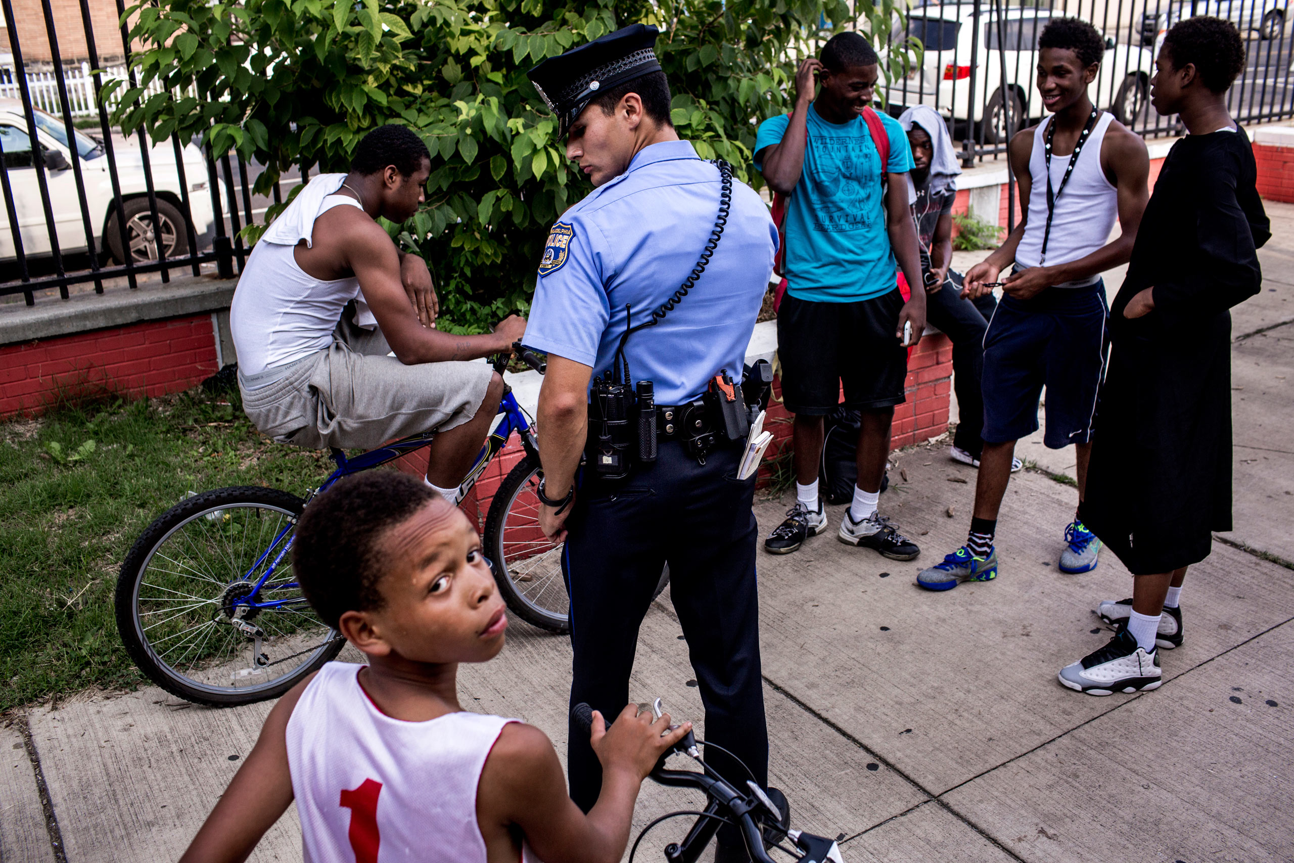 First year officer Jonathan Dedos (a  foot beat ) questions a group of young men, after a shooting suspect was described as an African-American  wearing white and on a bike, a description which could apply to many young men in the neighborhood. This group, at a local park, was vouched for by a man who works with local youth, and the police moved on. July 28, 2015. Philadelphia, Pa.
