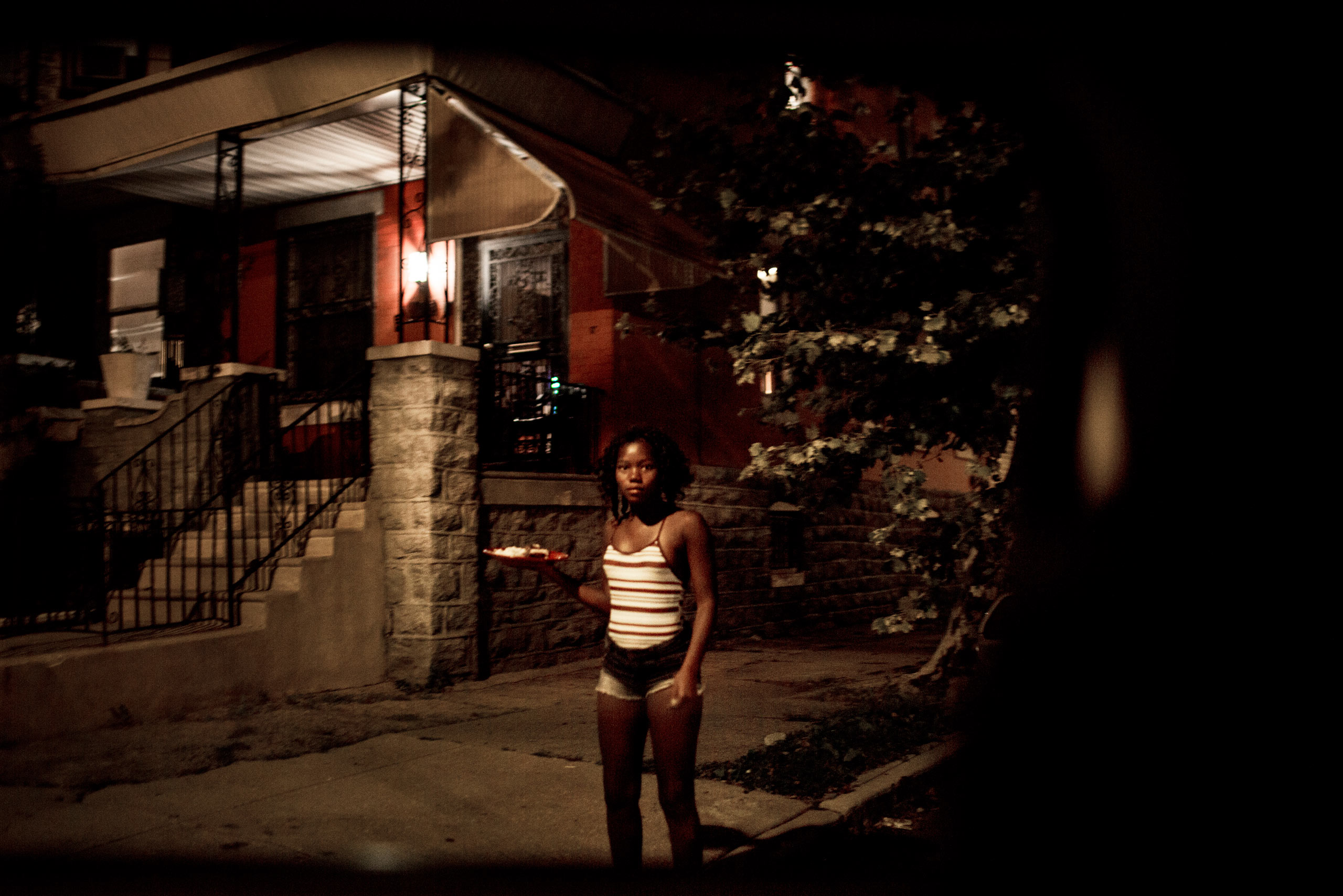 A young woman watches from a street corner in West Philadelphia as police drive by. July 28, 2015. Philadelphia, Pa.