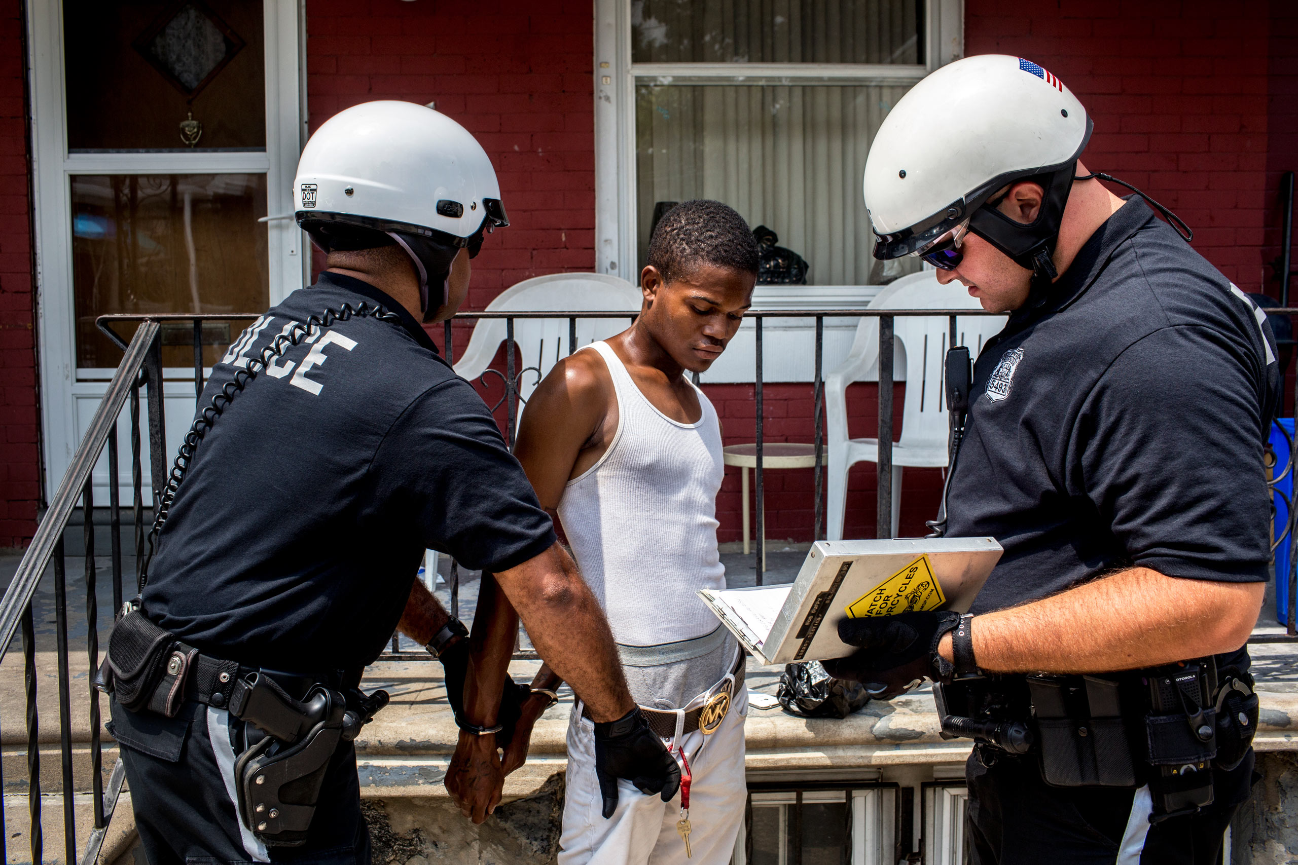 Officers Brian Dillard (left) and Robert Saccone (Right) detain a young man who fit the description of a criminal suspect in West Philadelphia. After being searched and questioned, the man was released. July 29, 2015. Philadelphia, Pa.