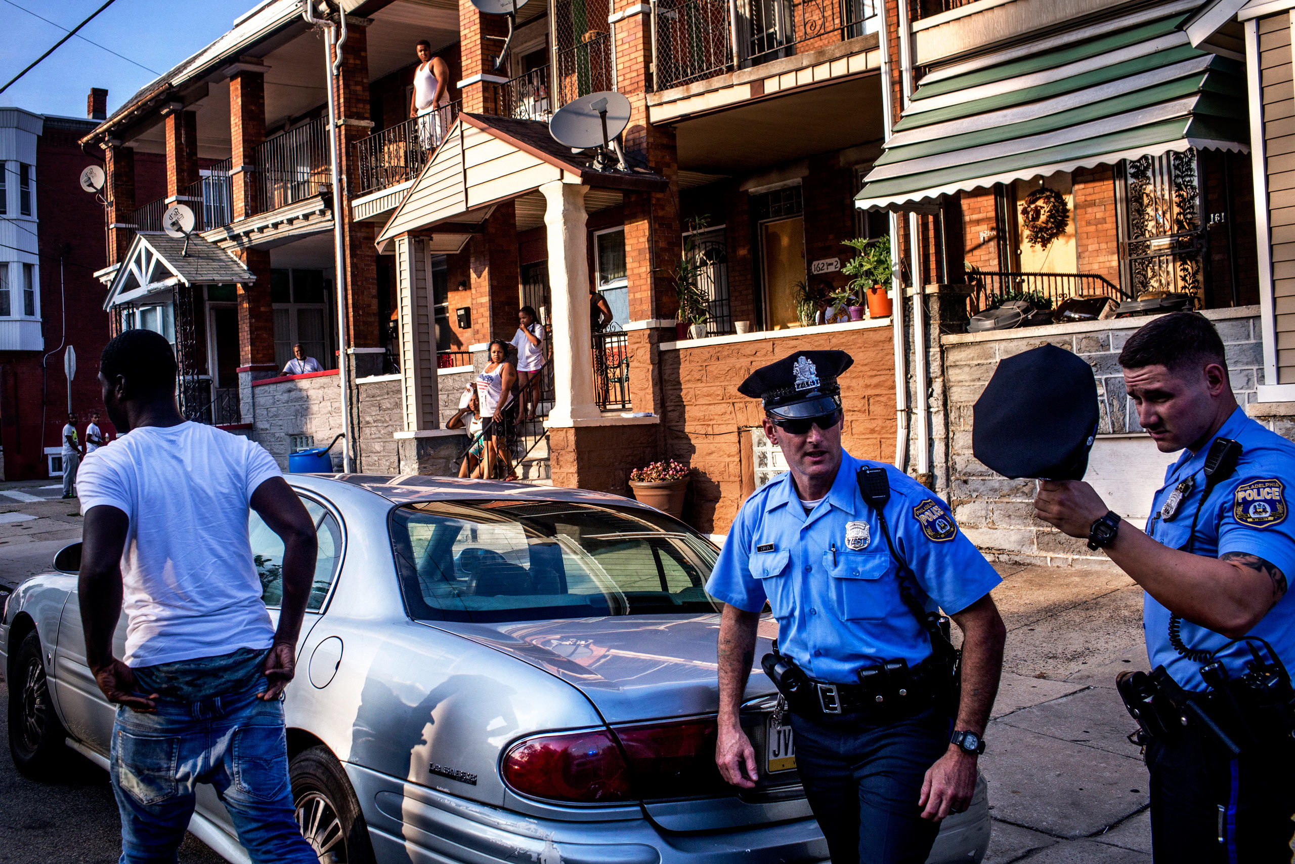 Officers Paul Watson, right, and his partner Officer Richard O'Brien make a traffic stop as neighbors look on. After the police searched his car, the man was released. July 29, 2015. Philadelphia, Pa.