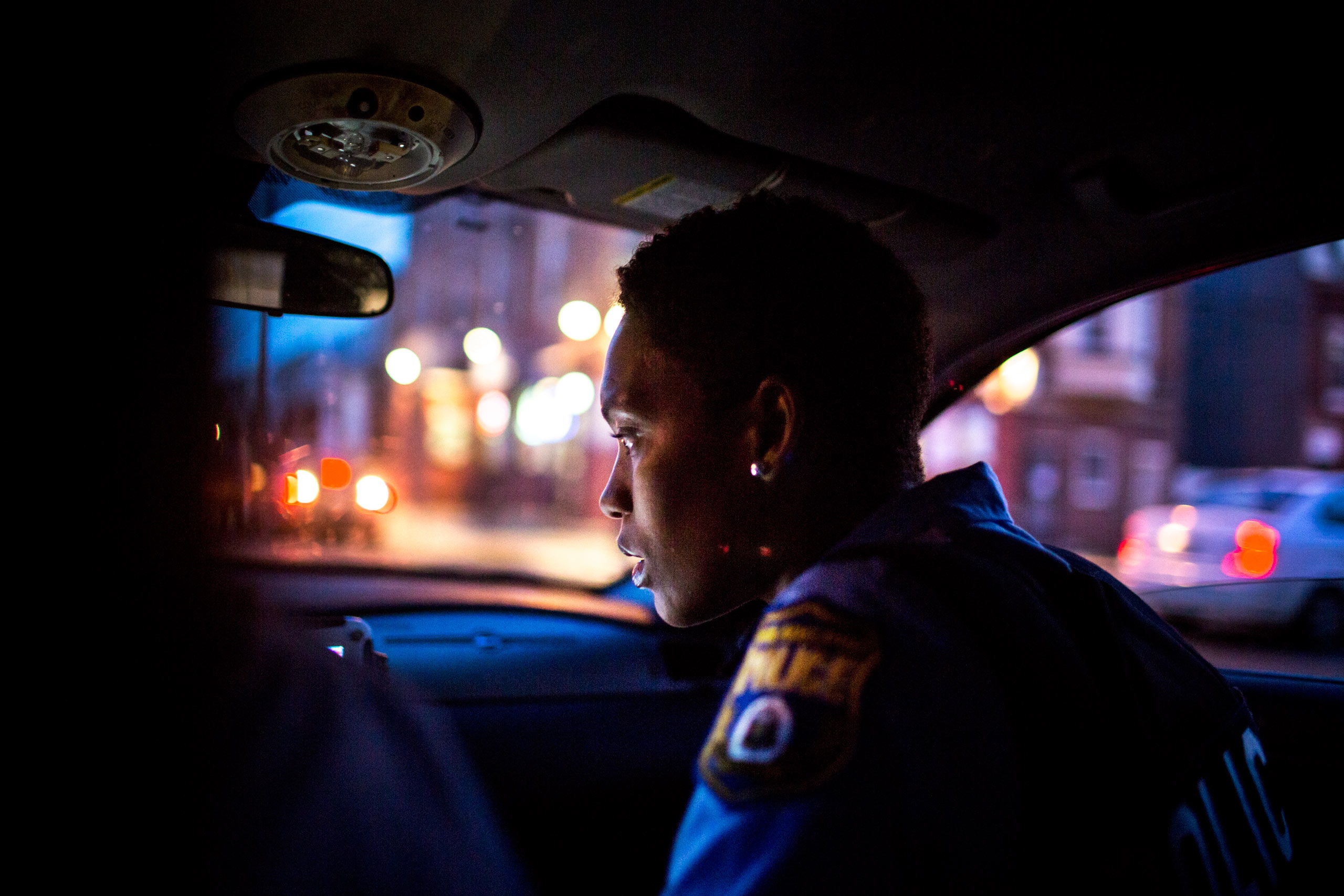 Officer Jade Howard inspects the patrol car's computer which gives information about incoming radio calls and suspects. July 29, 2015. Philadelphia, Pa.