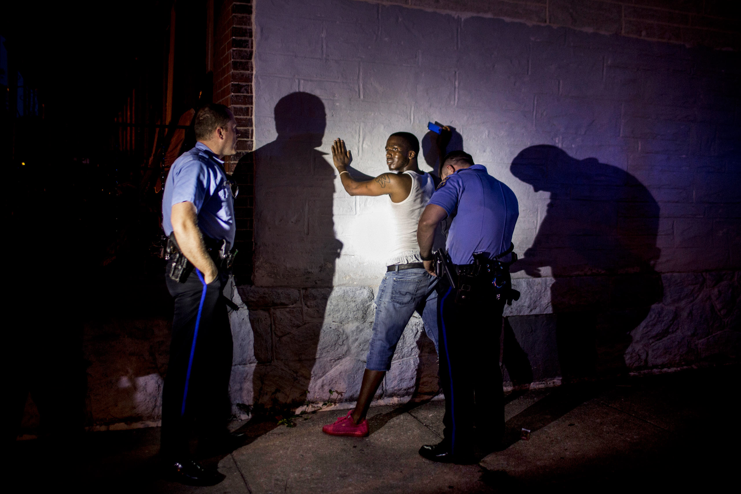A man is arrested for allegedly violating a Protection From Abuse order, by Officer Paul Watson, right, and his partner, Adam Womer. The man's case is pending judicial proceedings. July 29, 2015. Philadelphia, Pa.                                                              Correction: The original version of this caption misidentified the police officer on the left in this photograph. He is Officer Adam Womer.