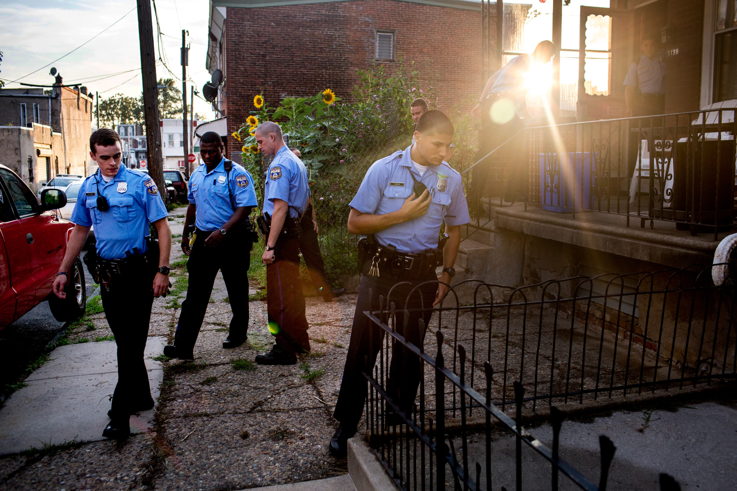 Officers search the scene for shell casings after reports of a man shooting off a shotgun to threaten his neighbor from his porch. As no one heard shots and there were no casings, police suspected the man had brandished the weapon but not fired it. July 30, 2015. Philadelphia, Pa.