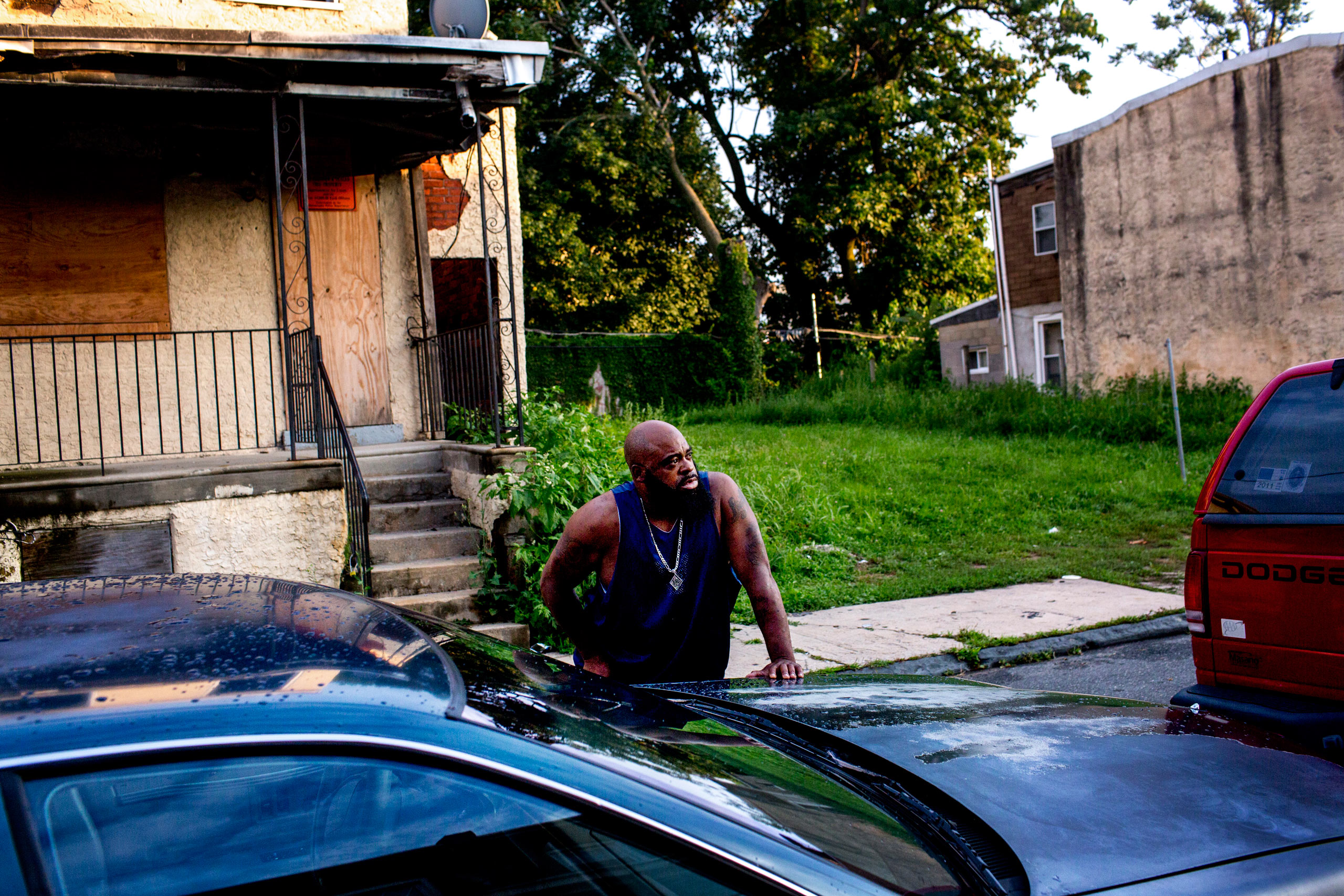 A neighbor watches as officers search the scene for shell casings after reports of a man shooting off a shotgun to threaten him from his porch. As no one heard shots and there were no casings, police suspected the man had brandished the weapon but not fired it. July 30, 2015. Philadelphia, Pa.