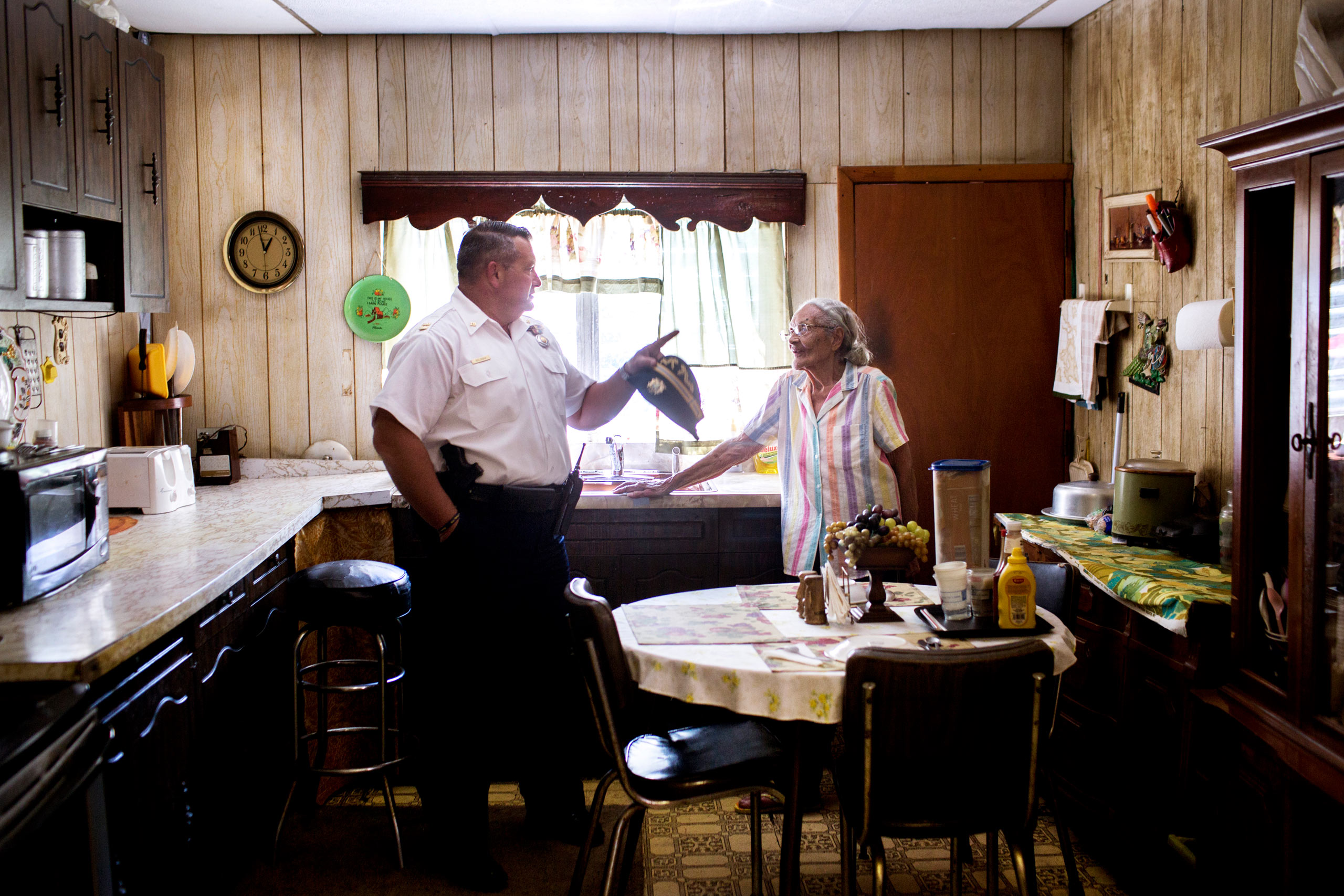 Captain Joe Bologna chats with Louise Robinson in her kitchen after she called him in off the street to look at a problem with overgrowth and vermine in the unkempt garden of an abandoned house behind her home. Robinson has lived in her home down the street from the 19th District station since the '50s, and says that hers was one of the first black families to move to the neighborhood. July 31, 2015. Philadelphia, Pa.