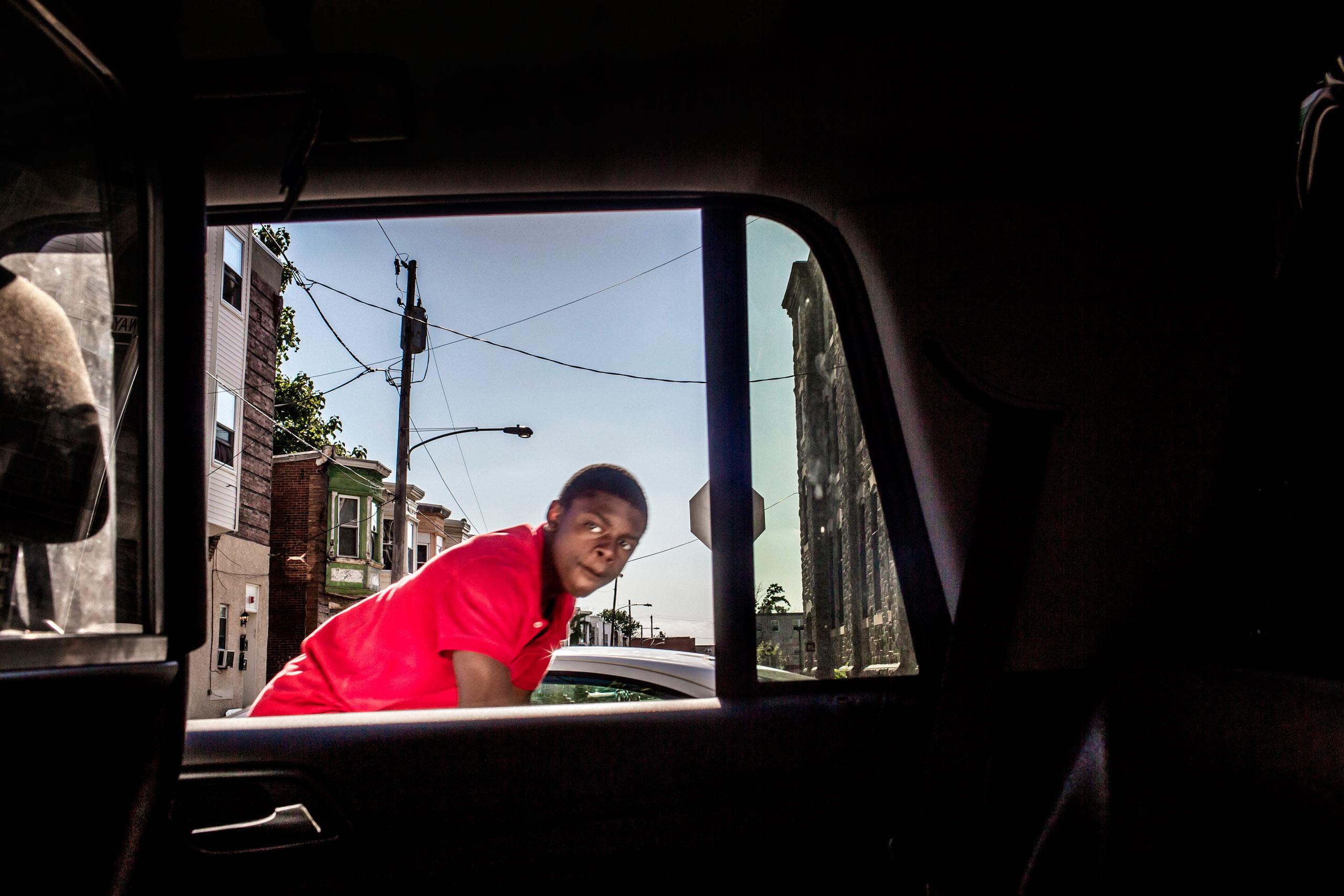 A boy rides by a patrol car on his bike. July 31, 2015. Philadelphia, Pa.