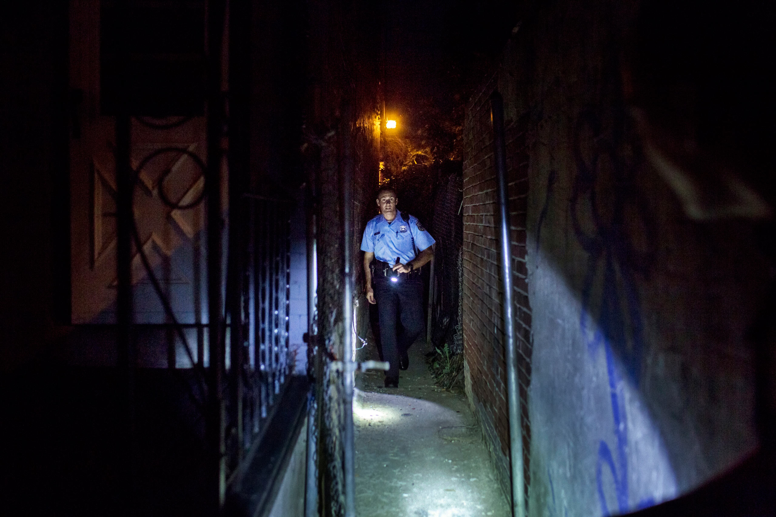 Officer Richard O'Brien searches an alley where a suspect had fled previously, searching for evidence he might have dropped items like drugs or weapons. He found nothing. July 31, 2015. Philadelphia, Pa.