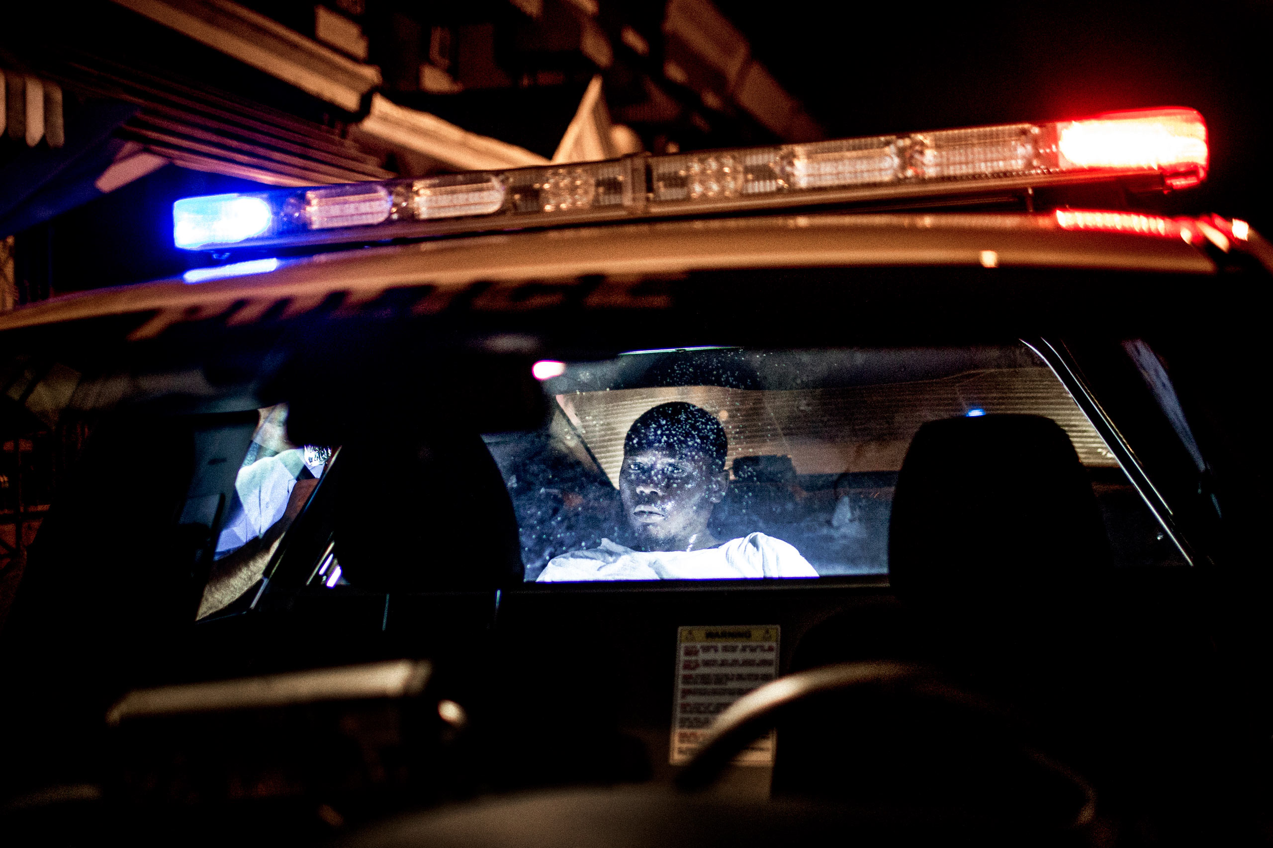 After running from the police and being caught, a young man recovers in the back of a patrol car. When asked why he ran he said he had had bad experiences with the police in the past. No evidence of criminal activity was found on him or nearby and he was ultimately released. July 31st, 2015. Philadelphia, Pa.