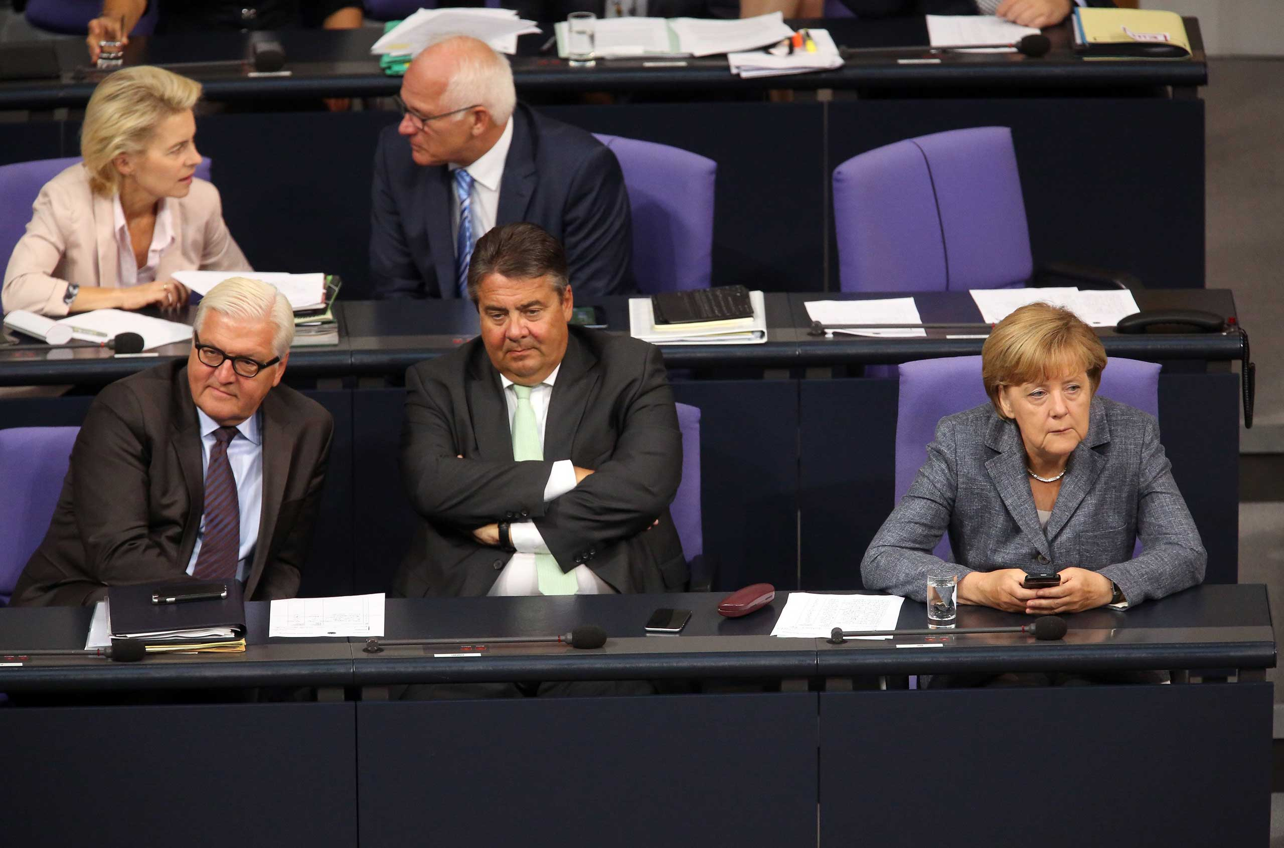 Foreign Minister Frank-Walter Steinmeier, Vice Chancellor and Economy and Energy Minister Sigmar Gabrie and German Chancellor Angela Merkel attend a meeting of the Bundestag, in Berlin, on Aug. 19, 2015.