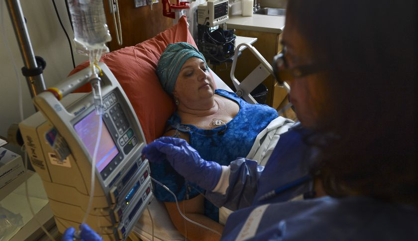 A nurse programs an infusion pump.