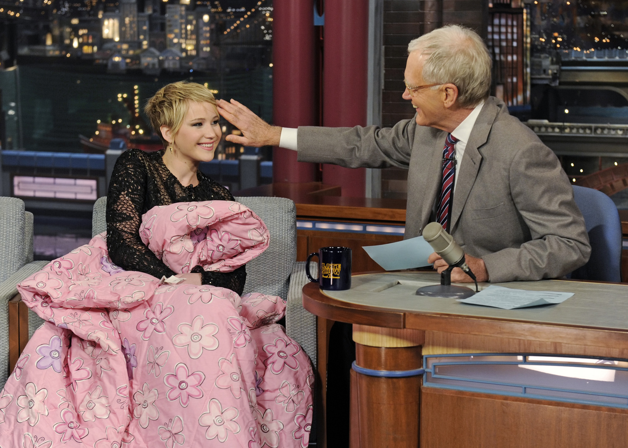Jennifer Lawrence gets cozy with Dave when she visits the <i>Late Show with David Letterman</i> on Nov. 20, 2013.