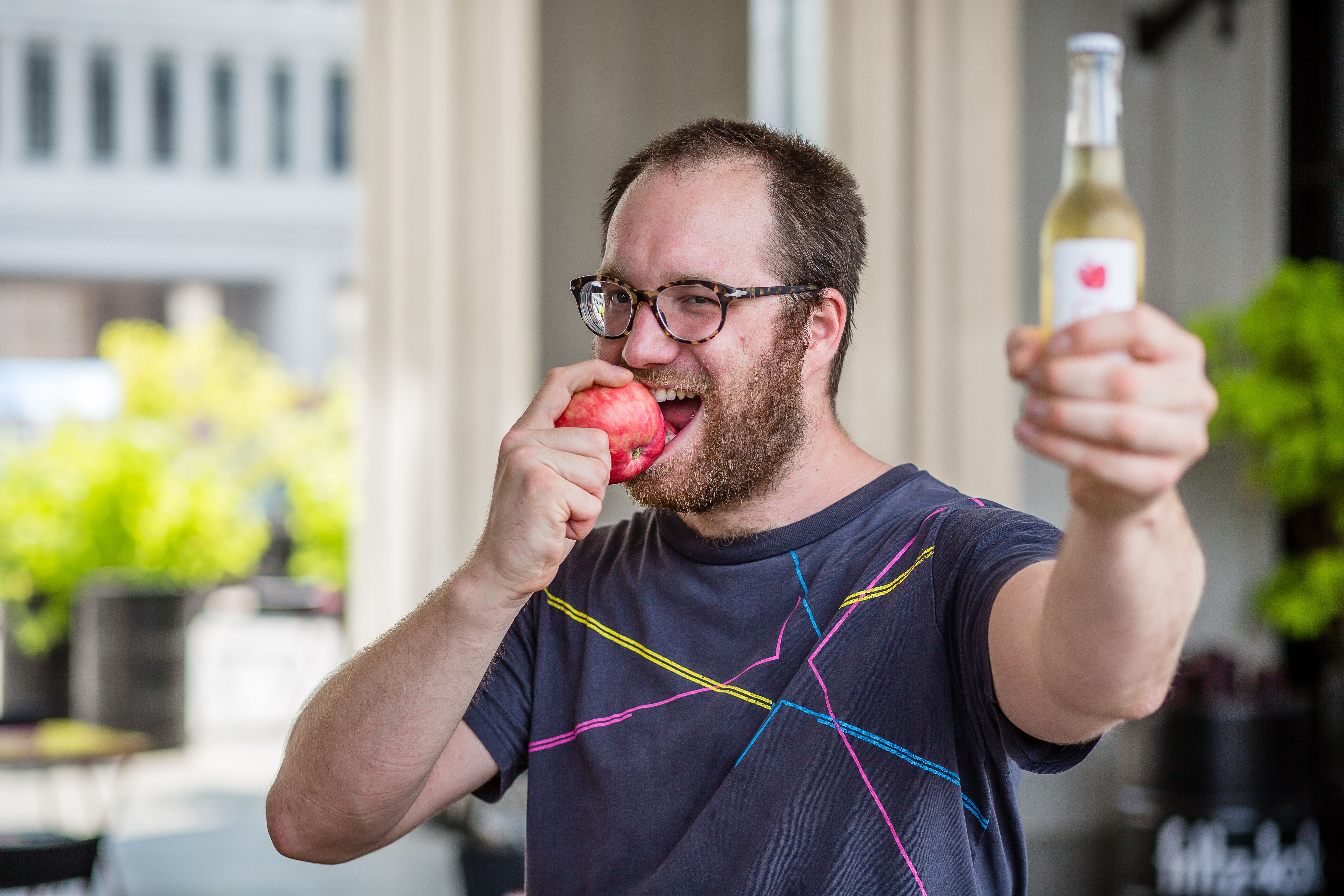 Jozef Czarnocki, owner of a popular Warsaw bar, is biting an apple and hoding a bottle of Polish cider to show his support for Twitter campaign  #eatapples to spite Putin , in Warsaw on July 31, 2014.