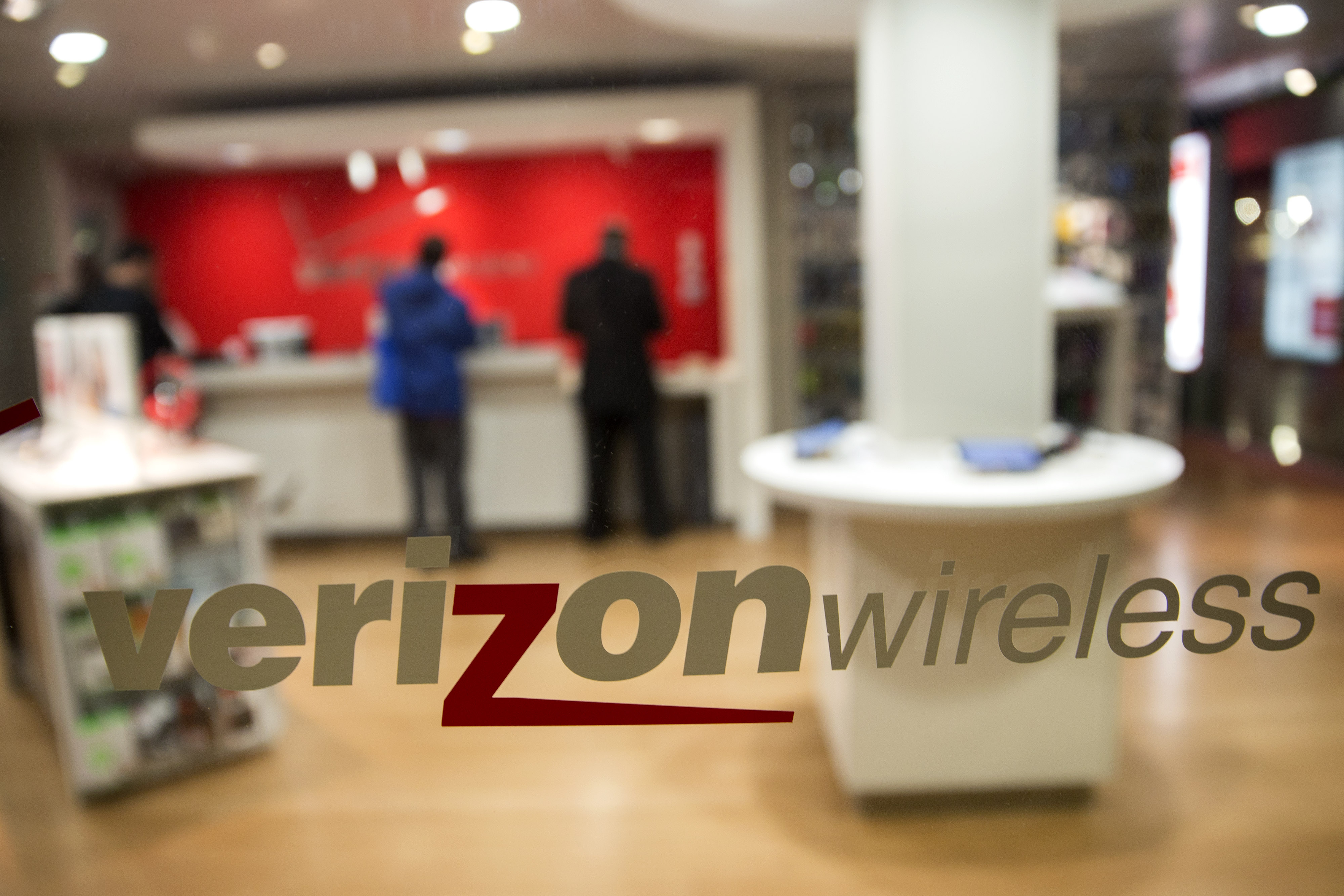 The Verizon Wireless logo is displayed on a window at a retail store in Washington, D.C. on Oct. 23, 2014.
